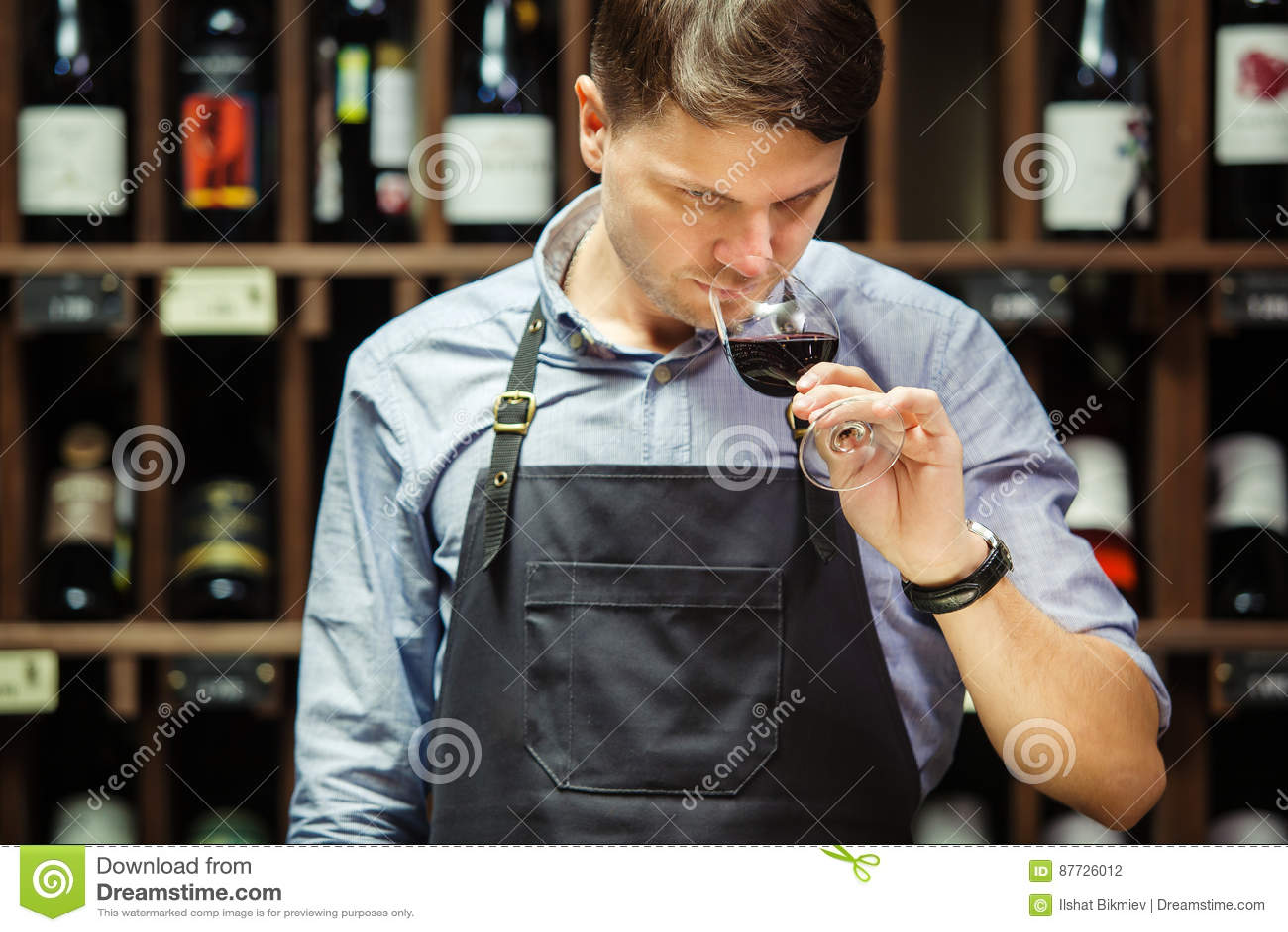 Bokal del vino rojo en el fondo, sommelier masculino que aprecia la bebida