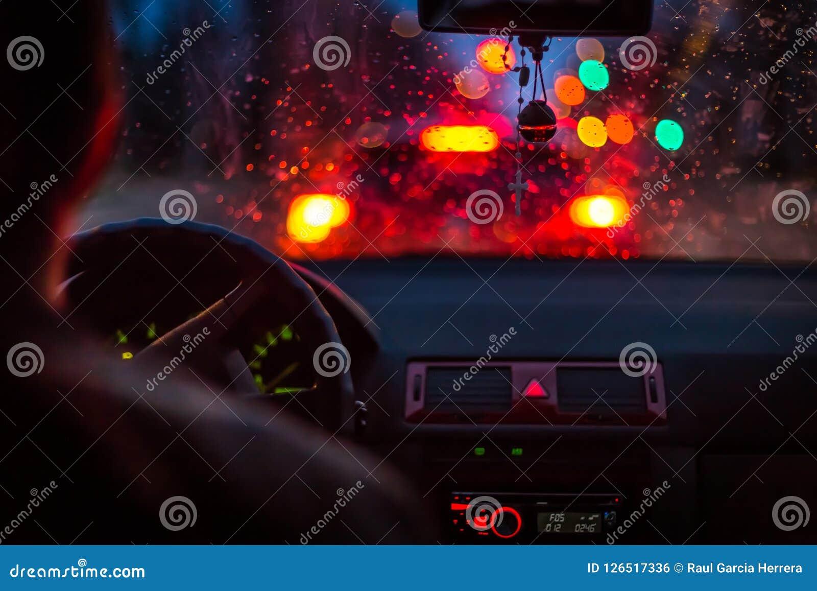 Bokeh si accende da ingorgo stradale tramite un tergicristallo dell automobile sulla notte piovosa nella grande città