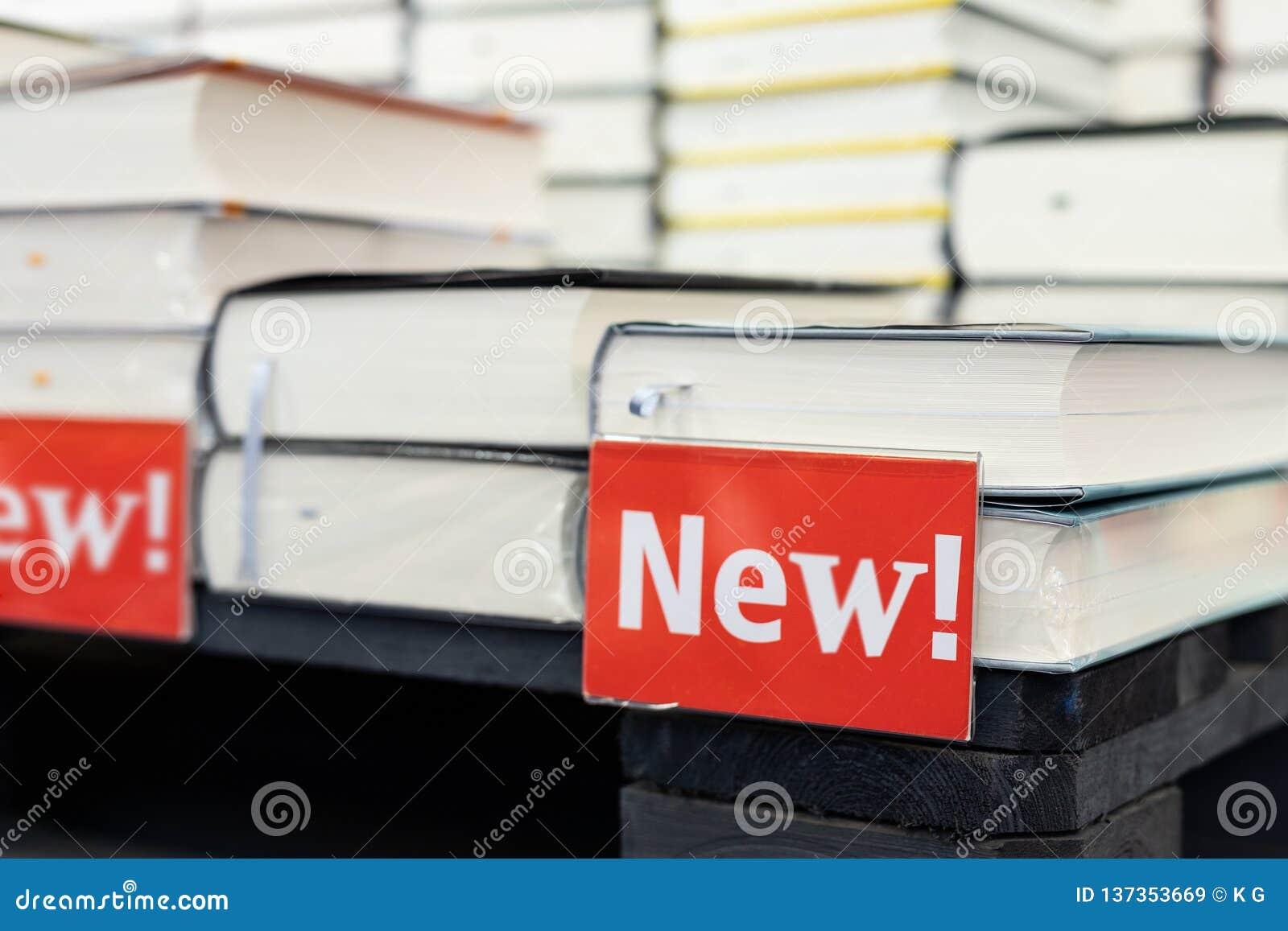 Bokhandelhylla med högen av nya böcker med den röda plattan Nya ankomster på bokhandeln Presentation av boken