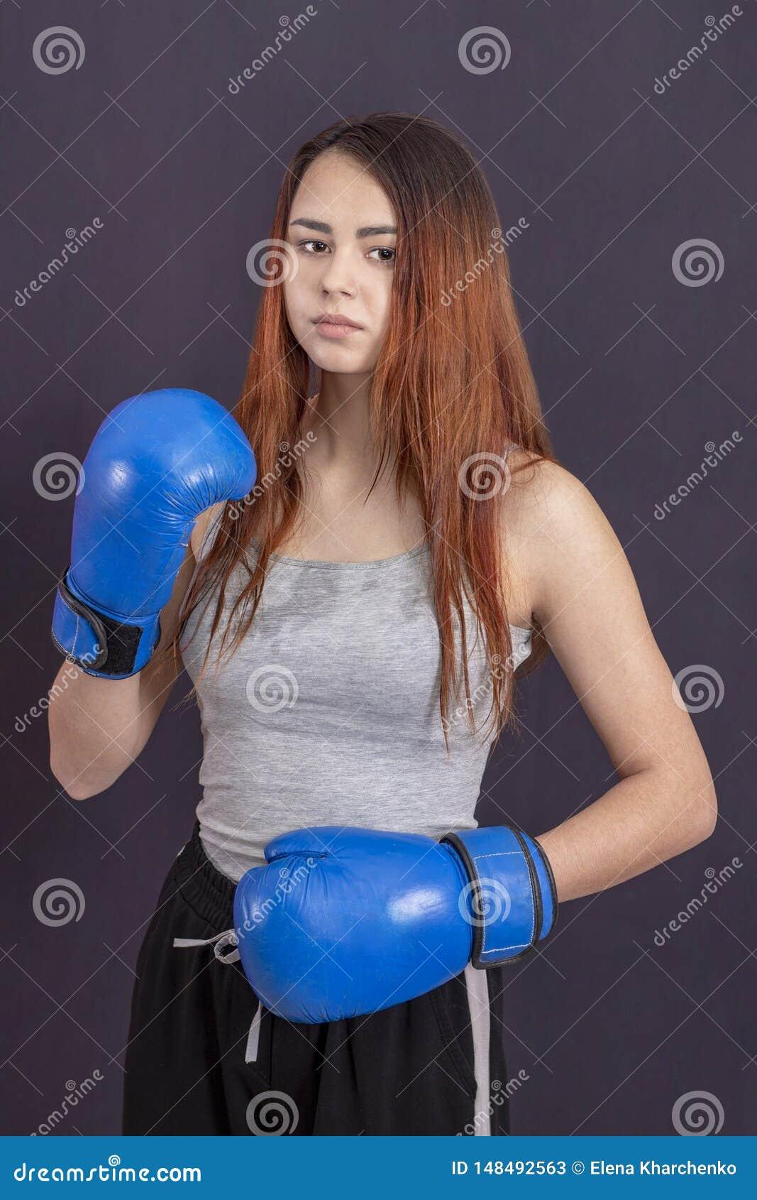 Bokser dziewczyna w b??kitnych bokserskich r?kawiczkach w szarej koszulce w stojaku