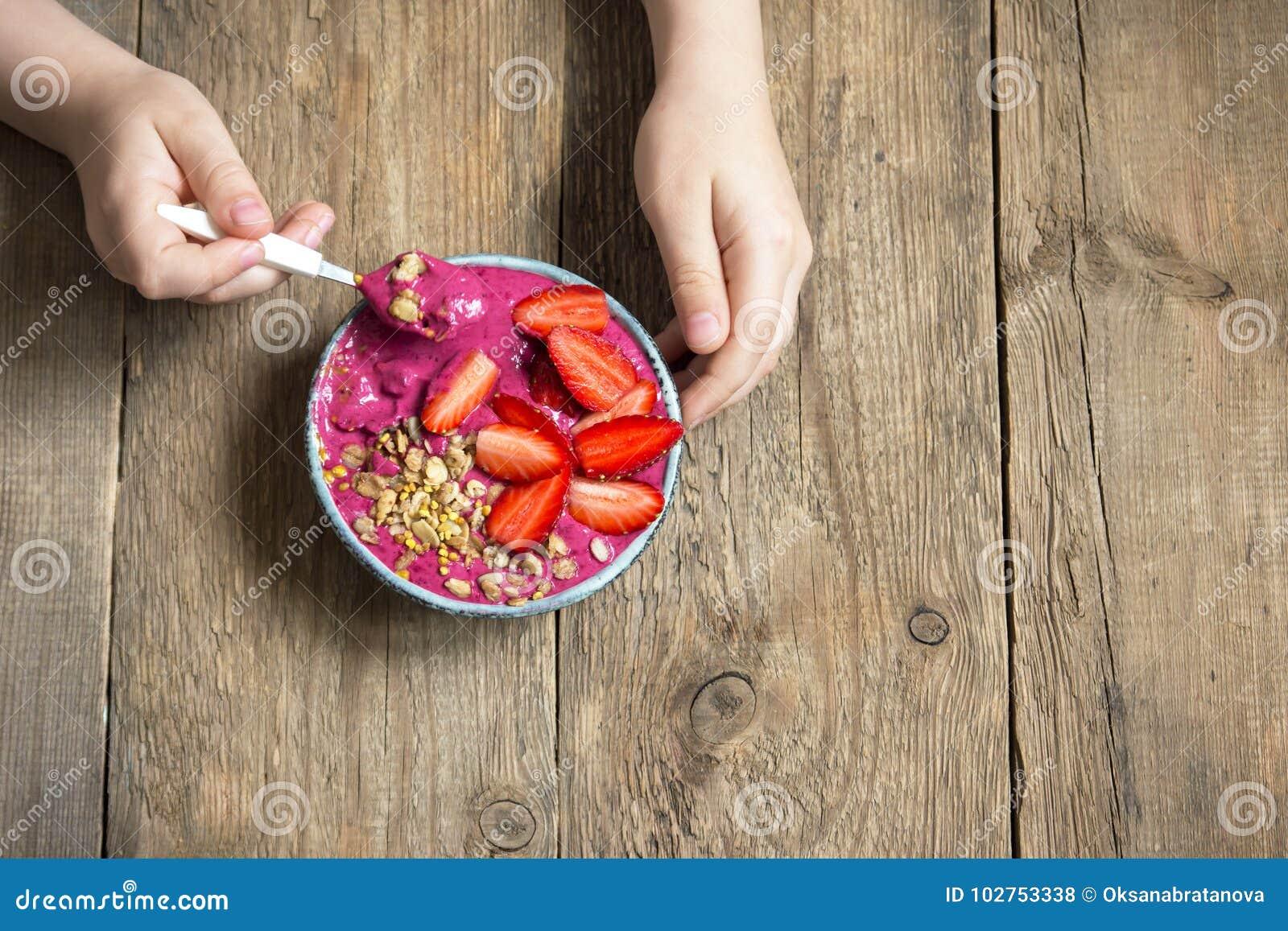 Bol de smoothie de petit déjeuner dans des mains