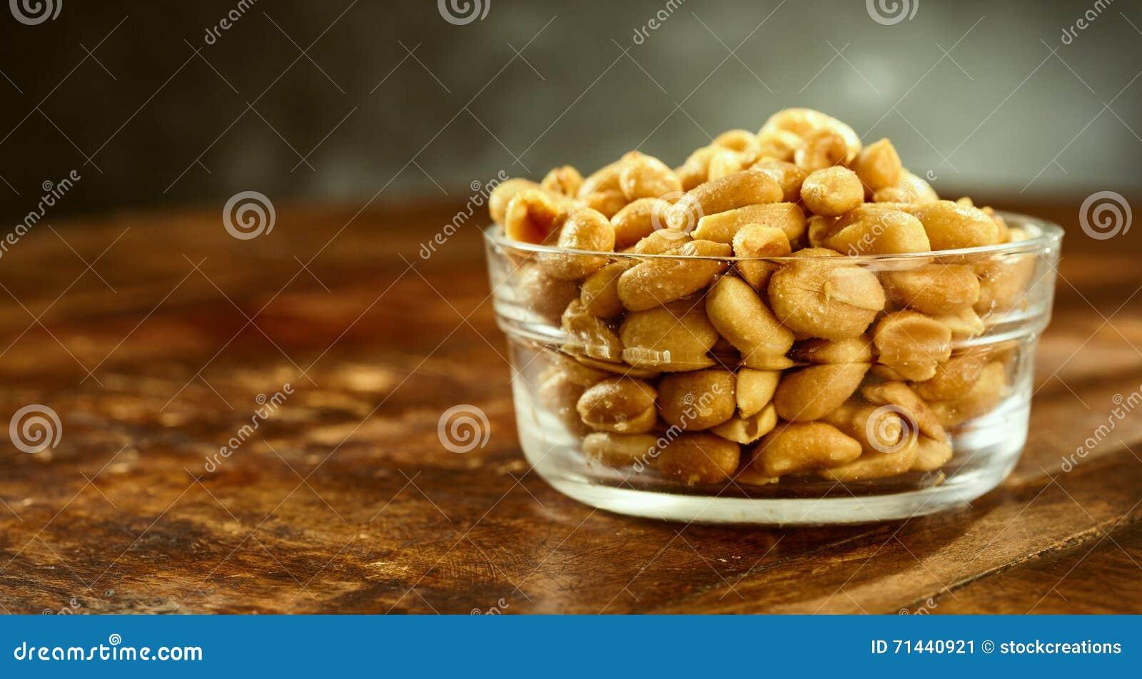 Bol de vidrio de cacahuetes salados asados frescos