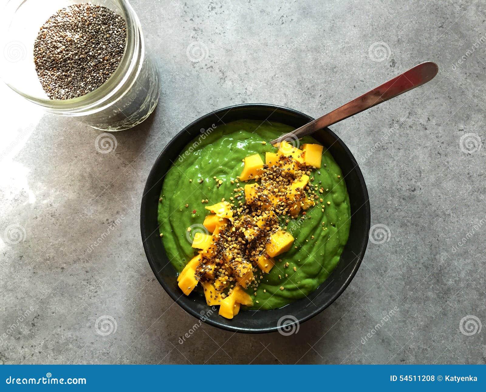 Bol vert de smoothie avec les graines coupées de mangue et de chia