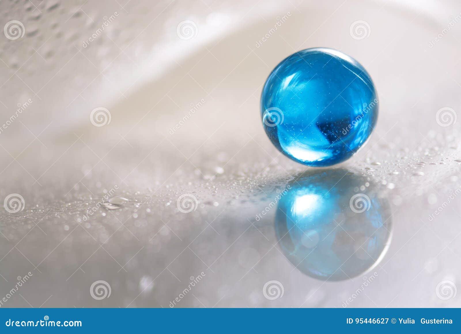 Bola azul de vidro em uma tabela de vidro branca Foto abstrata com vidro e reflexão