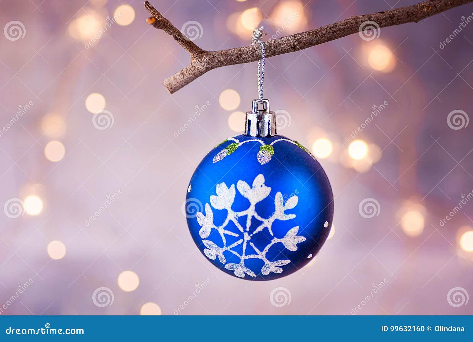 Bola azul del árbol de navidad con la ejecución del ornamento de la escama de la nieve en rama Luces de oro de la guirnalda brill