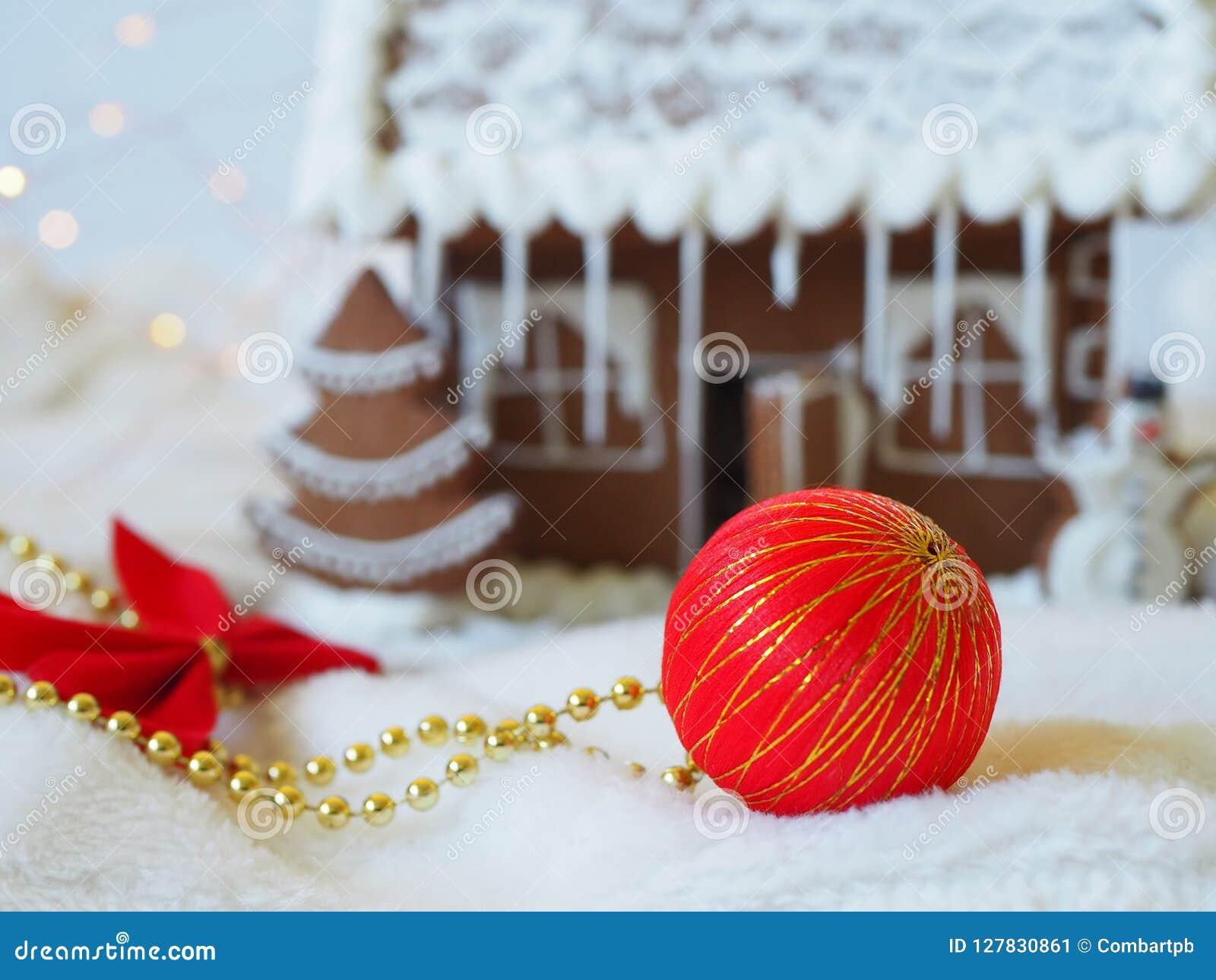 Bola de la Navidad delante de una casa de pan de jengibre en el fondo