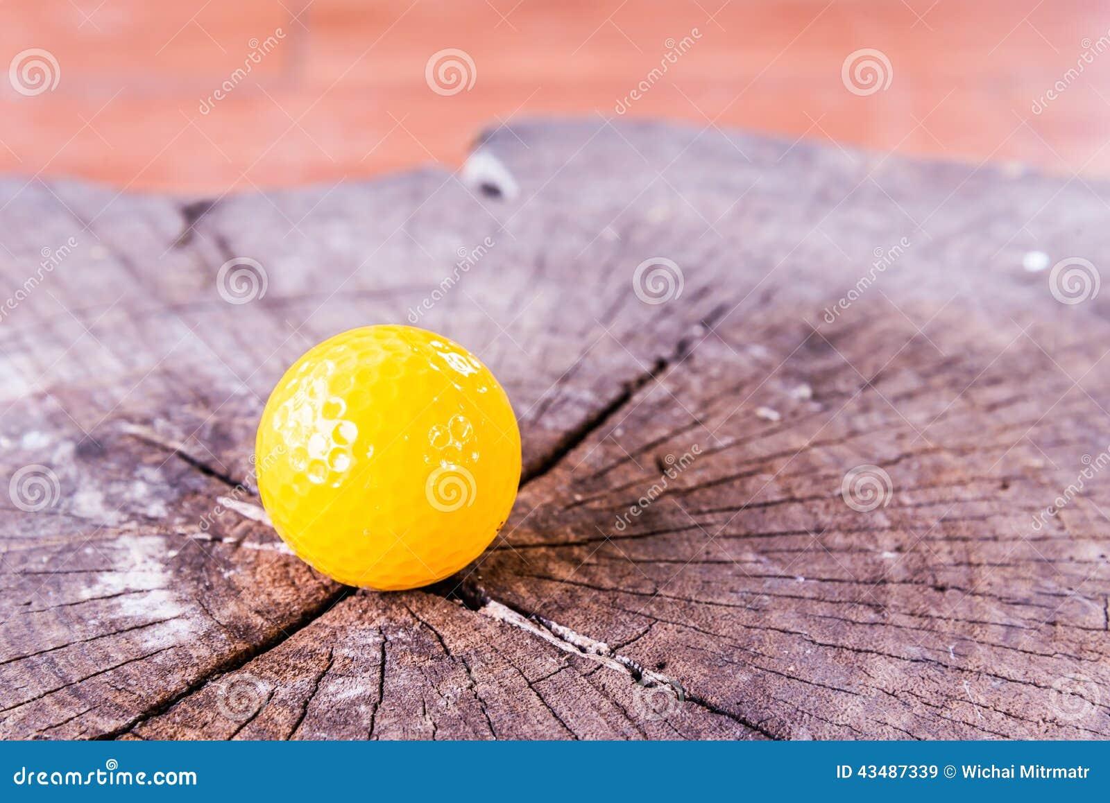 Bola de mini golfe amarela no fundo de madeira