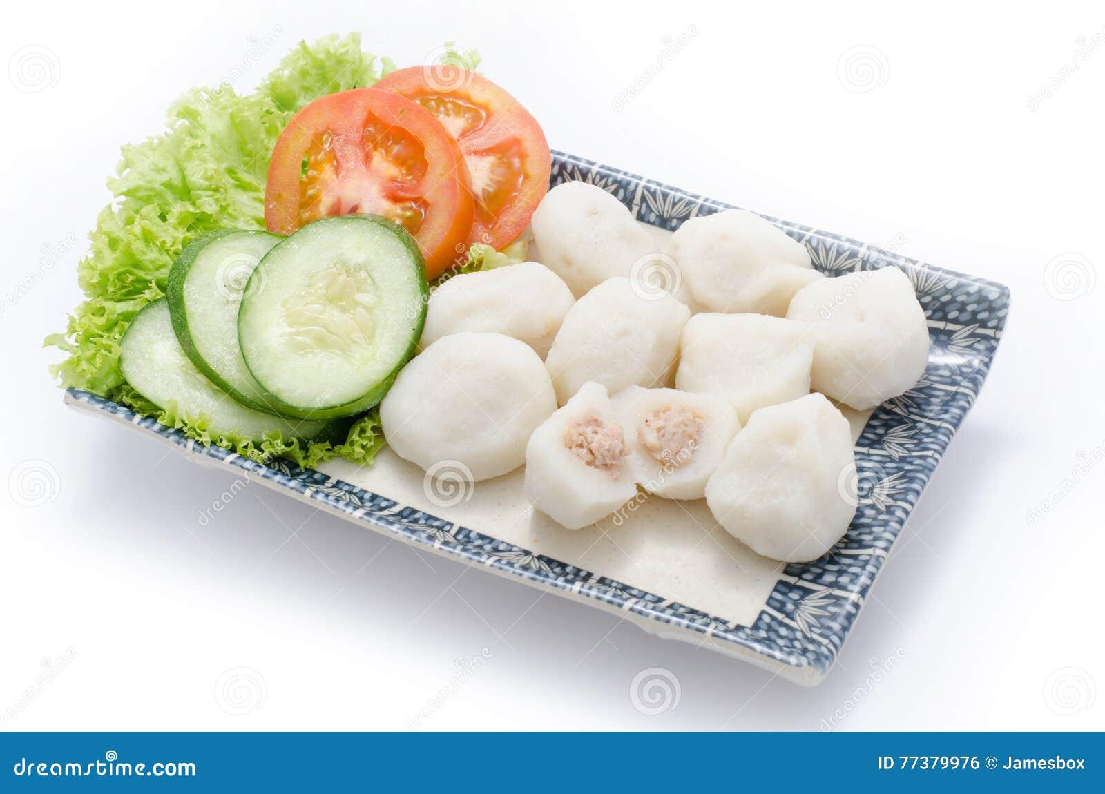 Bola de pescados con la carne y el pepino cortado, tomate, hebs en la placa