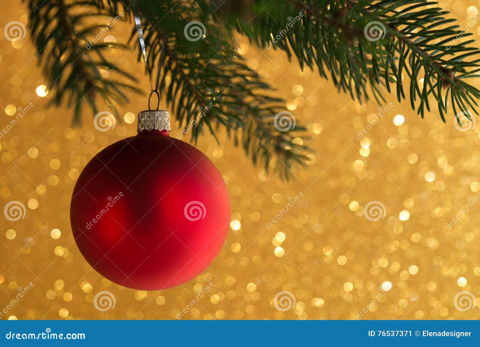 Bola decorativa vermelha na árvore do xmas no fundo do bokeh do brilho Cartão do Feliz Natal
