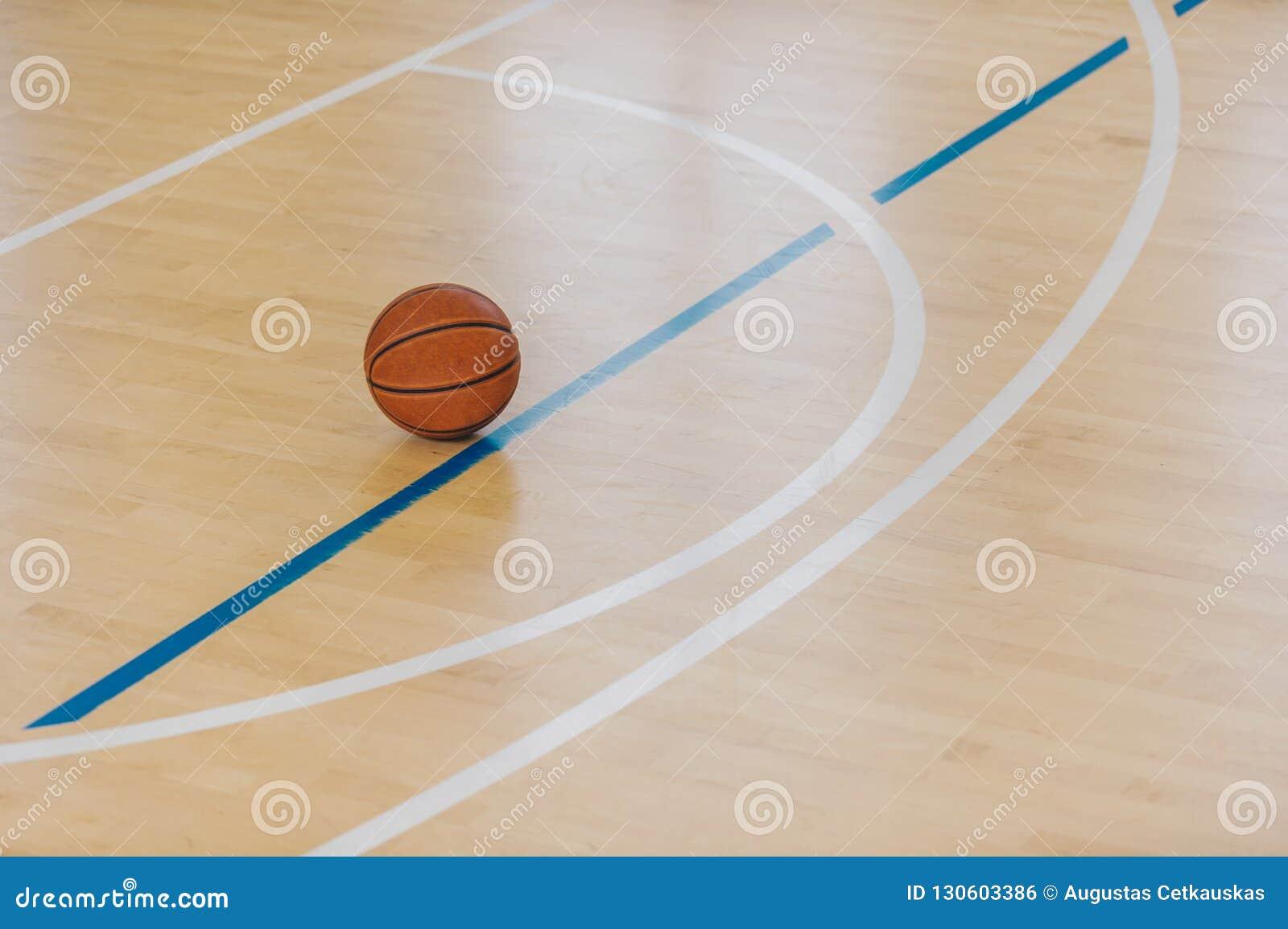 Bola do basquetebol sobre o assoalho no gym