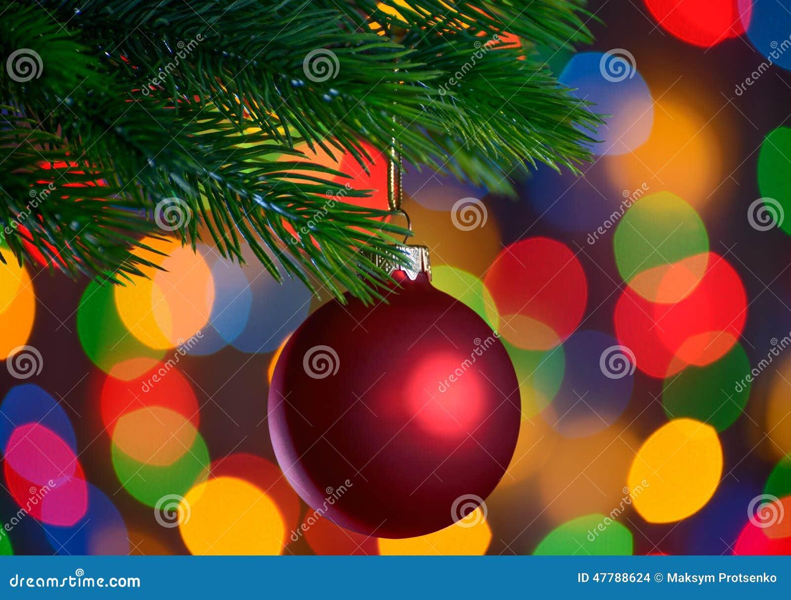 A bola do Natal no ramo do abeto no feriado ilumina o fundo