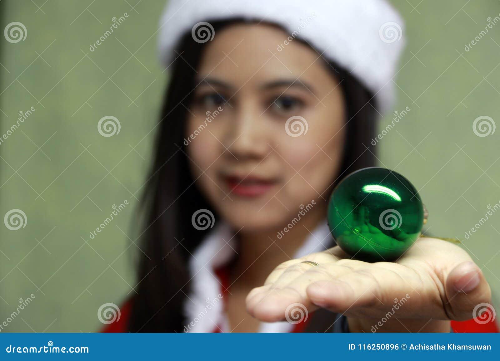 A bola mágica verde na mão de para fora focaliza o asiático Santa Girl Dress