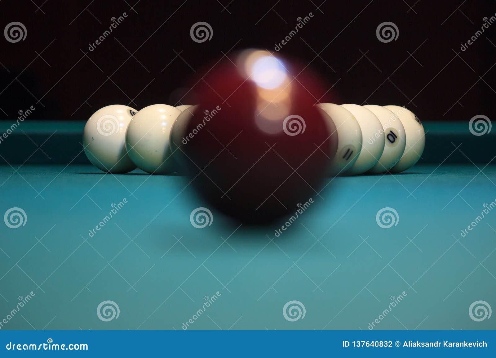 Bola marrón que miente en una mesa de billar verde el tiempo antes del juego la reflexión de la lámpara en el cuenco
