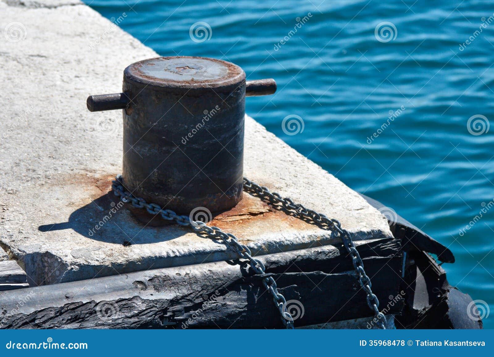 Bolardo del amarre con la cadena en el embarcadero
