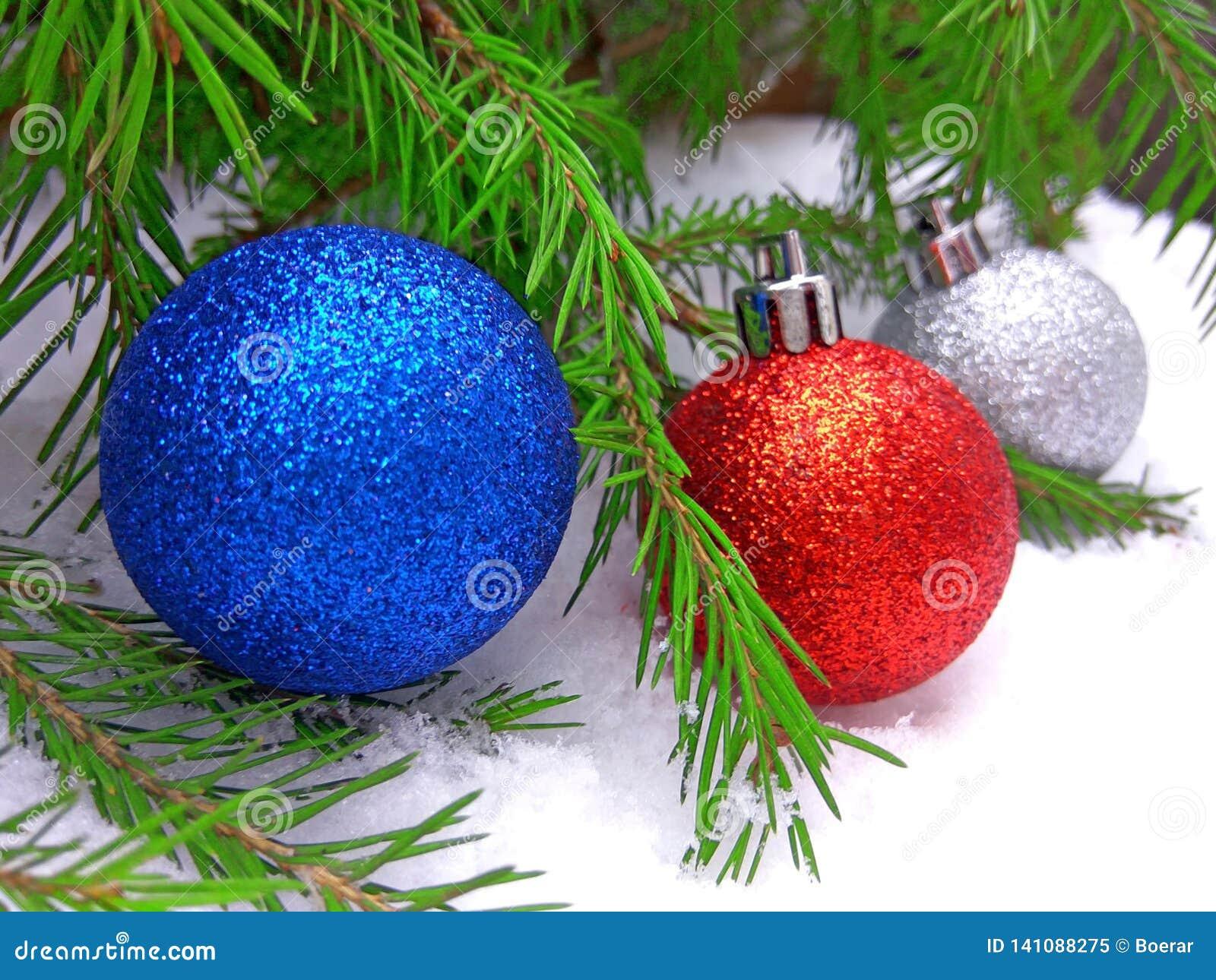 Bolas azuis, vermelhas e de prata do ano novo com a árvore de abeto verde no fundo nevado