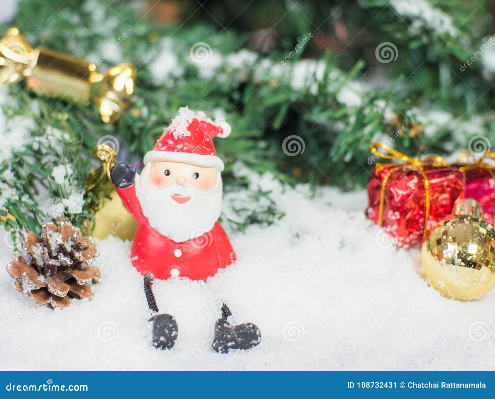 Bolas da boneca de Papai Noel e do Natal do glod e caixa vermelha no sno