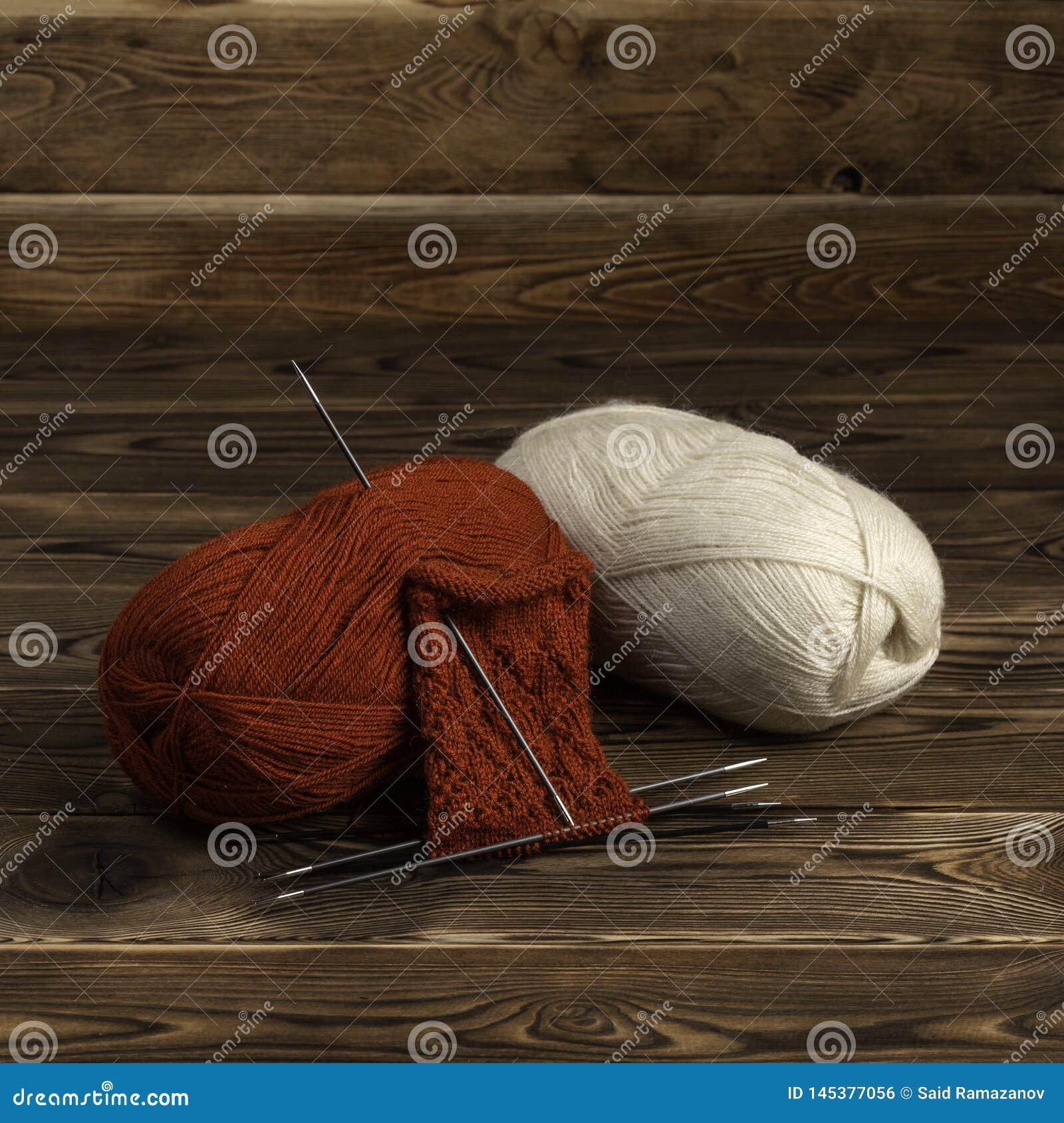 Bolas de agulhas da linha e de confecção de malhas com uma confecção de malhas em um fundo de madeira