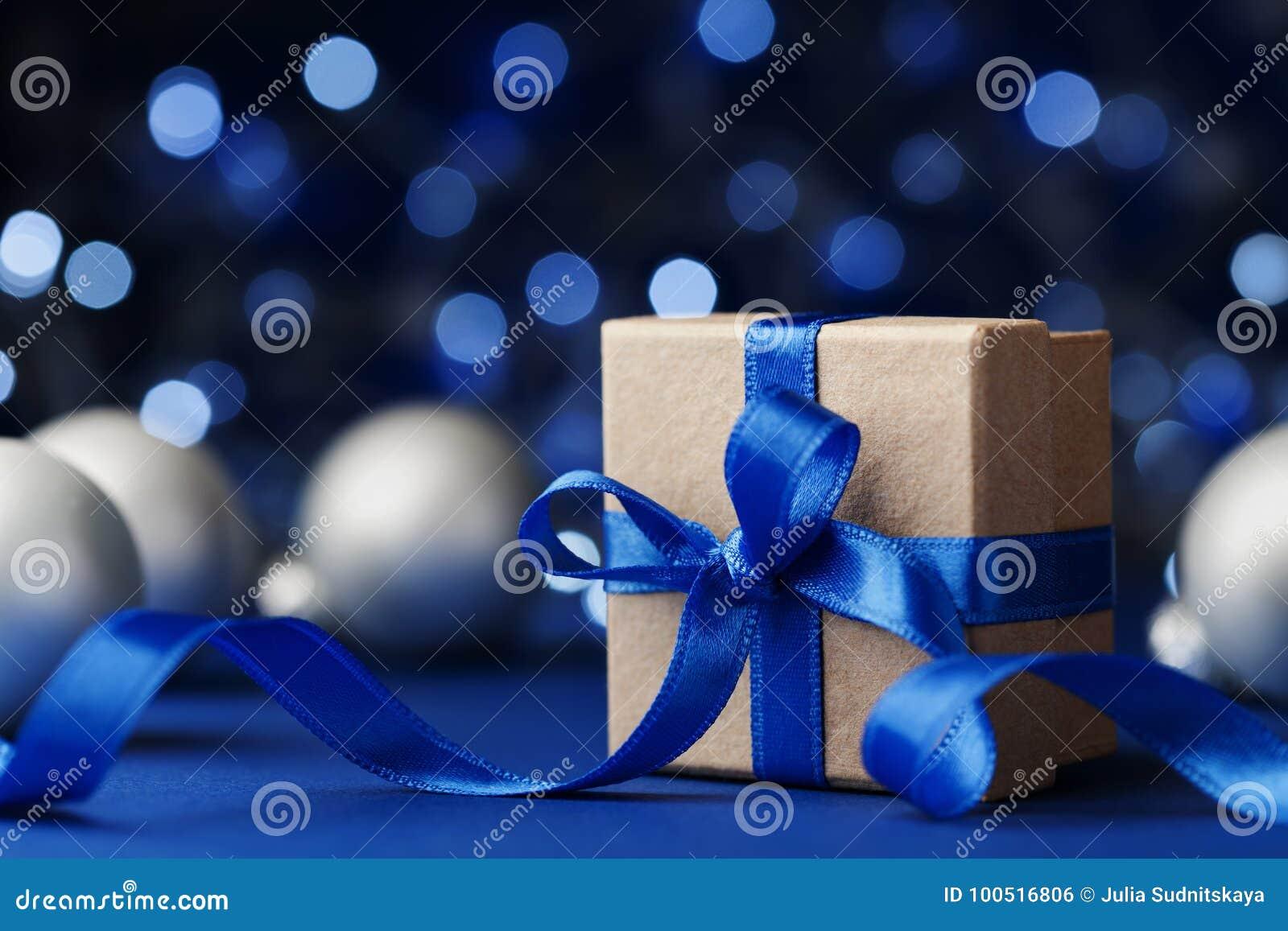 Bolas de la caja de regalo o del presente y de la Navidad contra fondo azul del bokeh Tarjeta de felicitación mágica del día de f