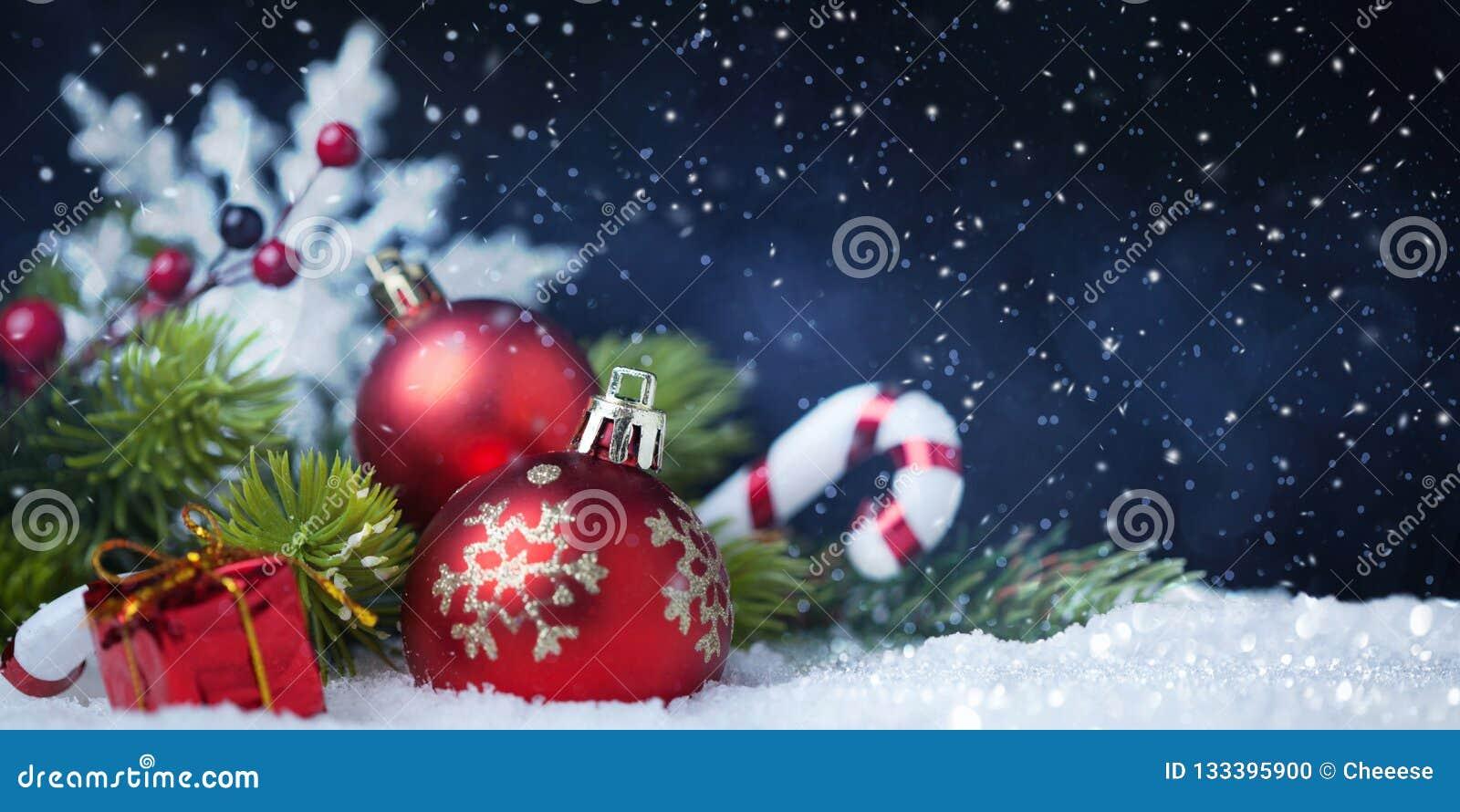Bolas de la Navidad con el árbol y decoraciones en nieve