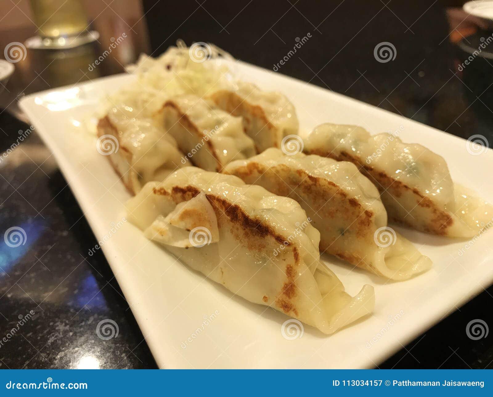 Bolas de masa hervida de Gyoza en el plato blanco, japonés popular
