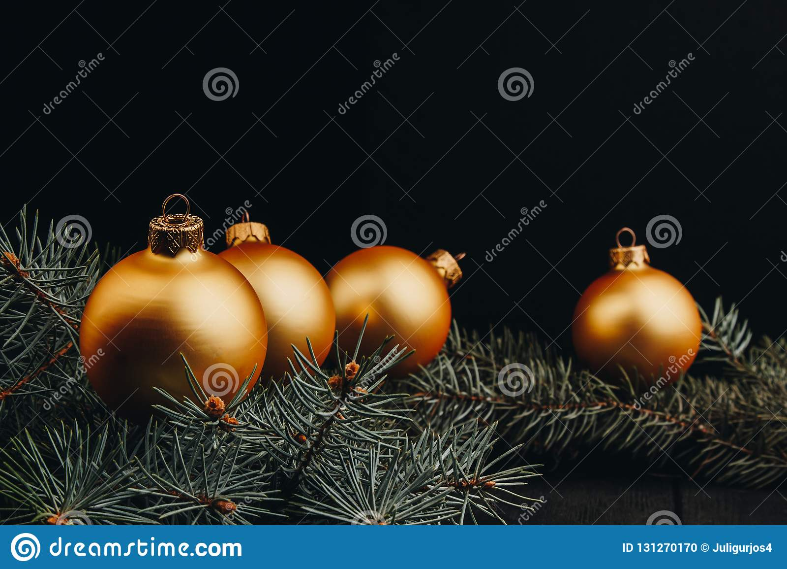 Bolas de oro de las decoraciones del juguete de la Navidad o del Año Nuevo y rama de árbol de la piel rústica en el fondo de made