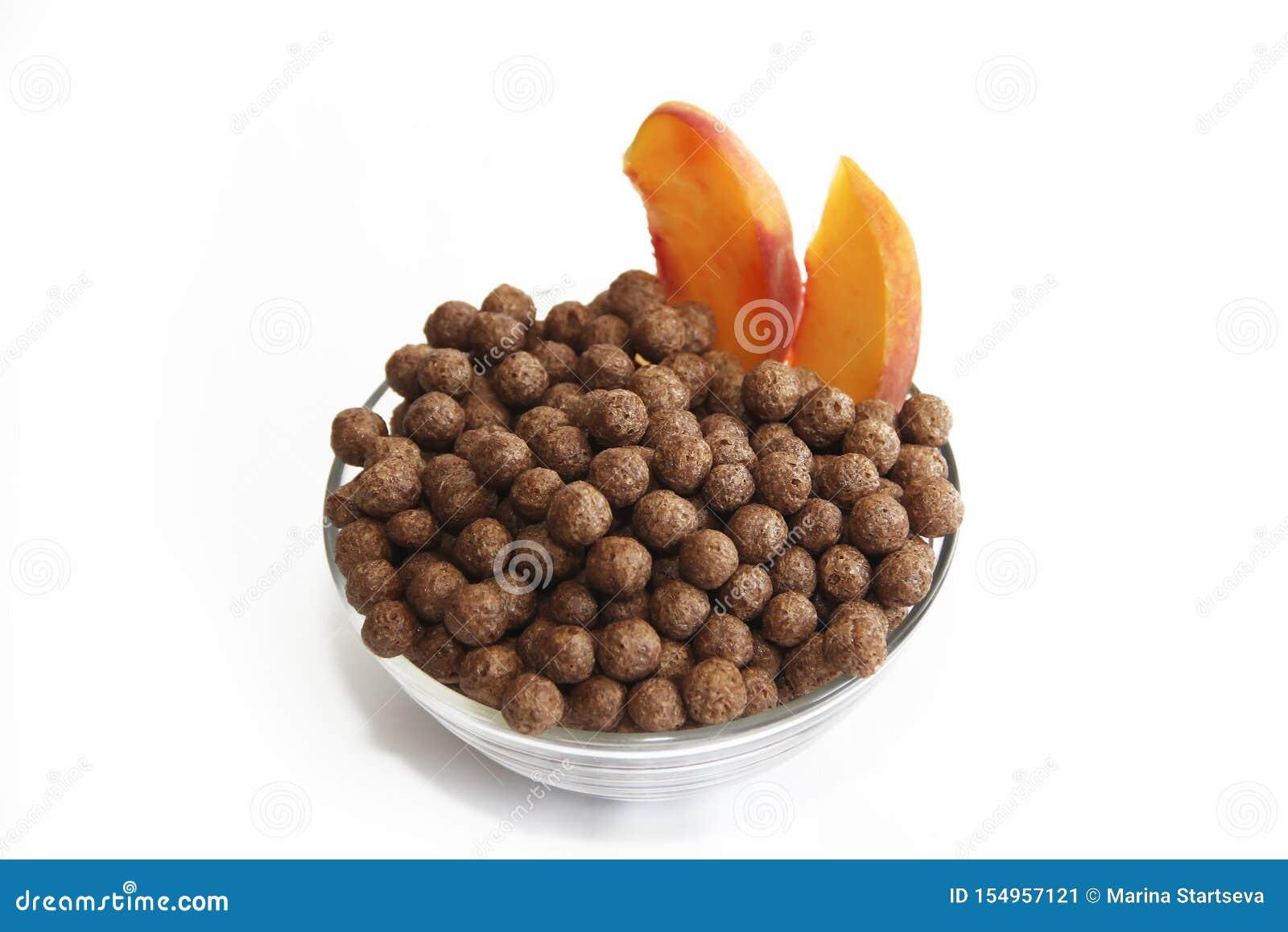 Bolas del maíz del chocolate dulce en la placa de cristal y el melocotón en un fondo blanco