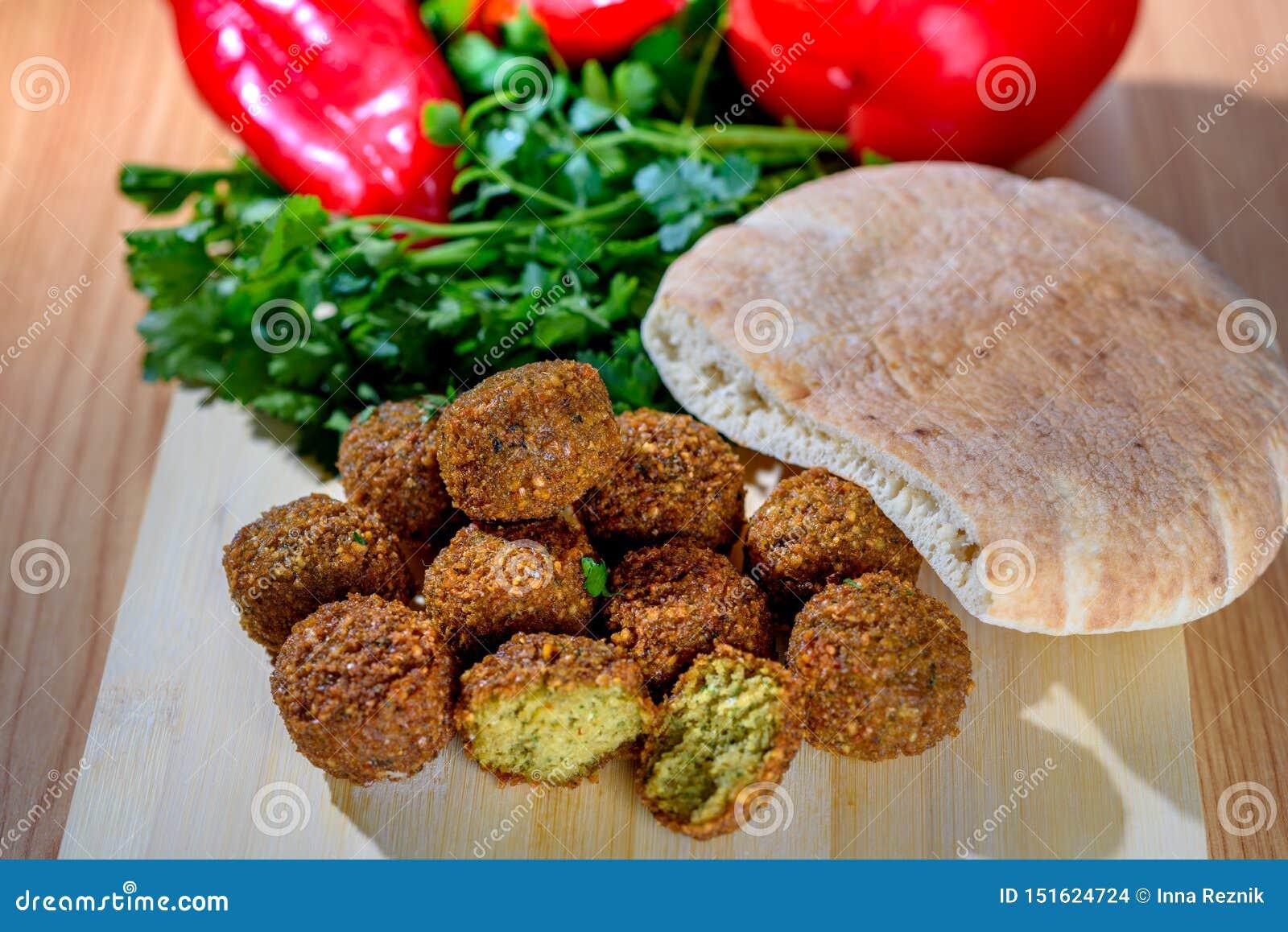 Bolas do Falafel, pimenta vermelha doce, pão pão árabe-árabe e salsa fresca verde no fundo rústico de madeira