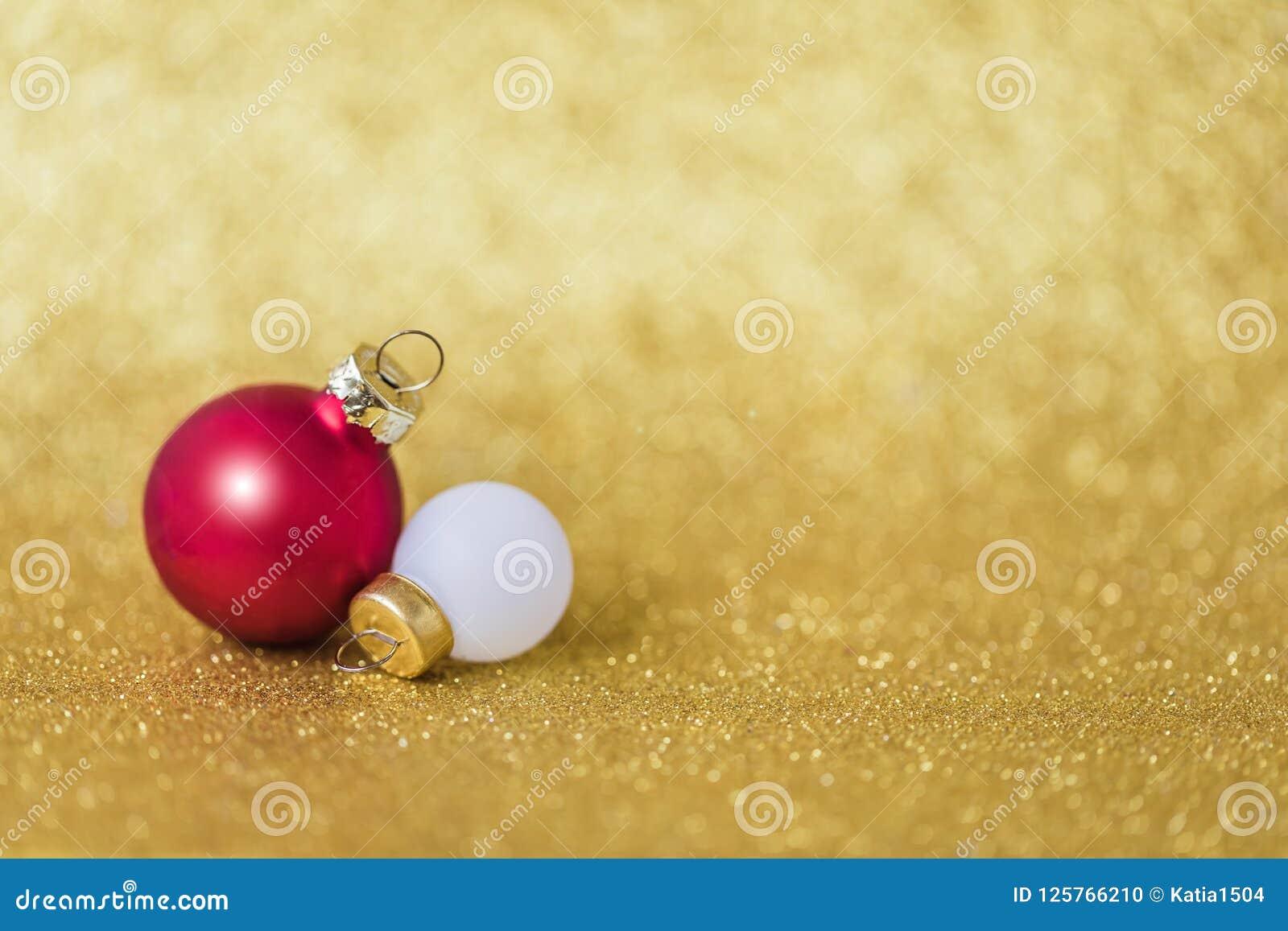 Bolas mates blancas y rojas de la Navidad en el fondo de oro chispeante, foco selectivo