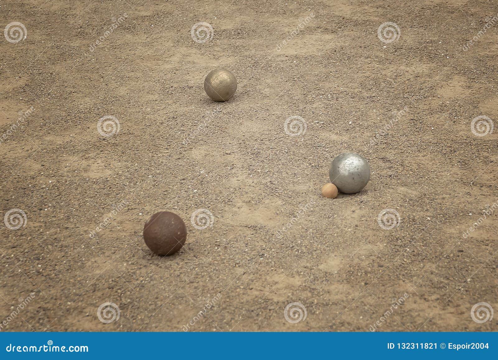 Bolas metálicas viejas del petanque en campo de piedra fino