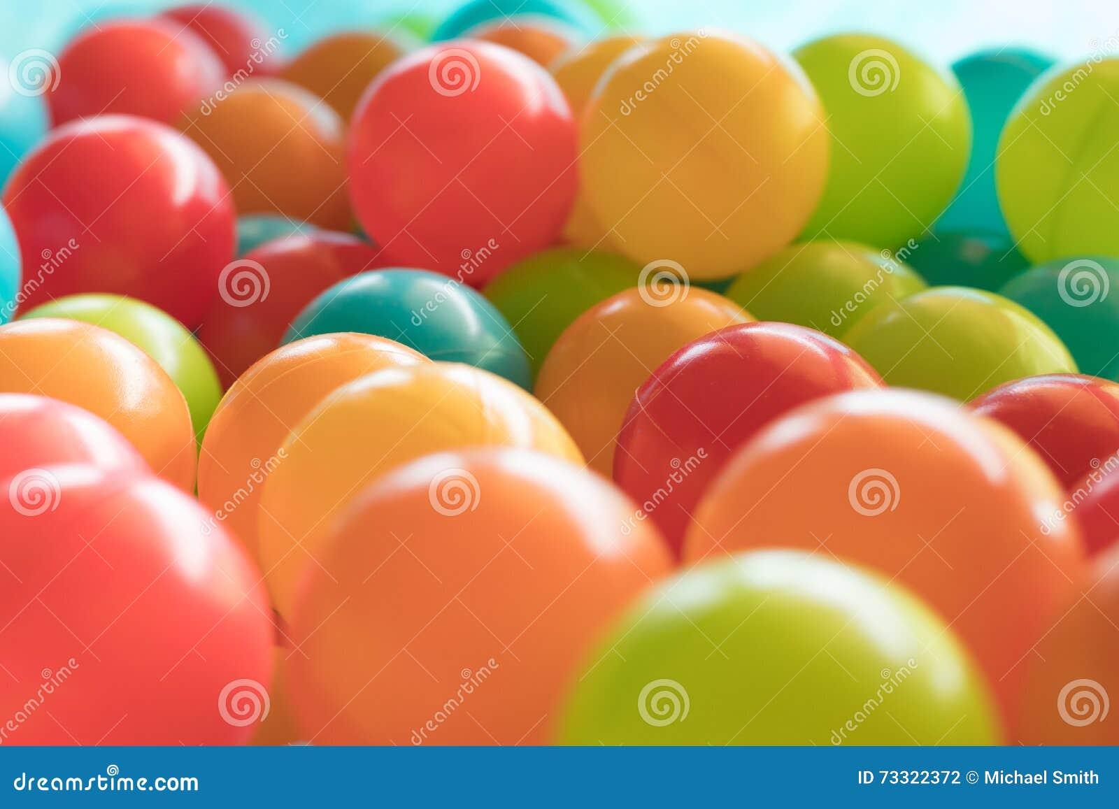 Bolas plásticas brilhantes e coloridas do brinquedo, poço da bola, fim acima