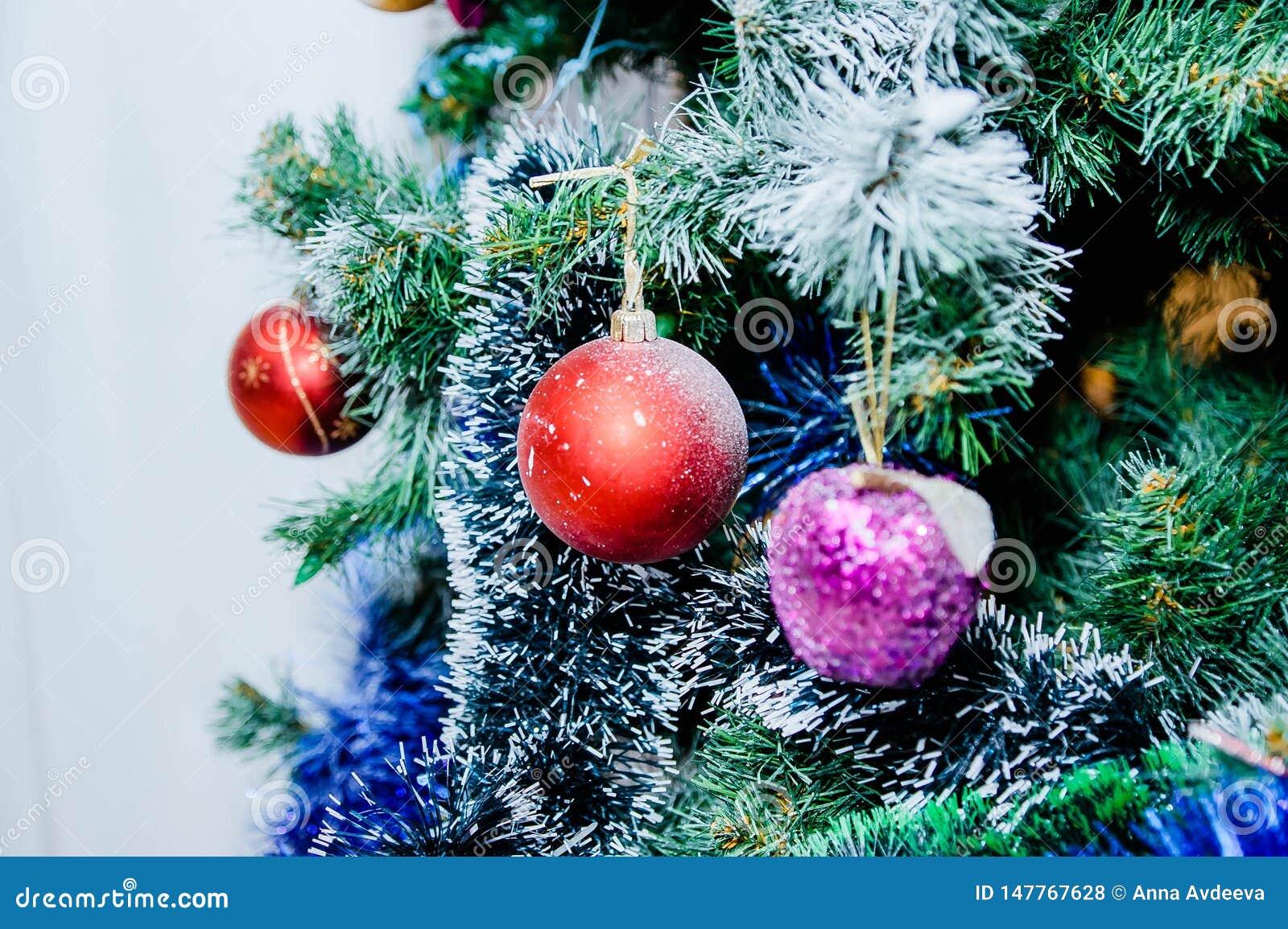 Bolas rojas y púrpuras y guirnalda blanca y azul en un árbol de navidad