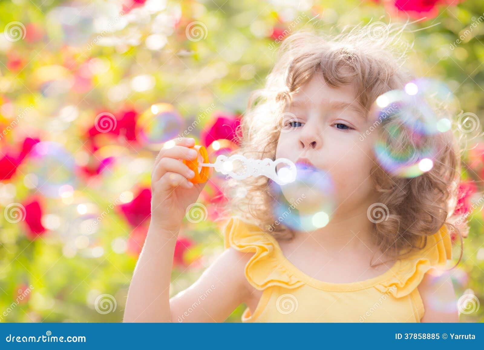Bolhas de sabão de sopro da criança
