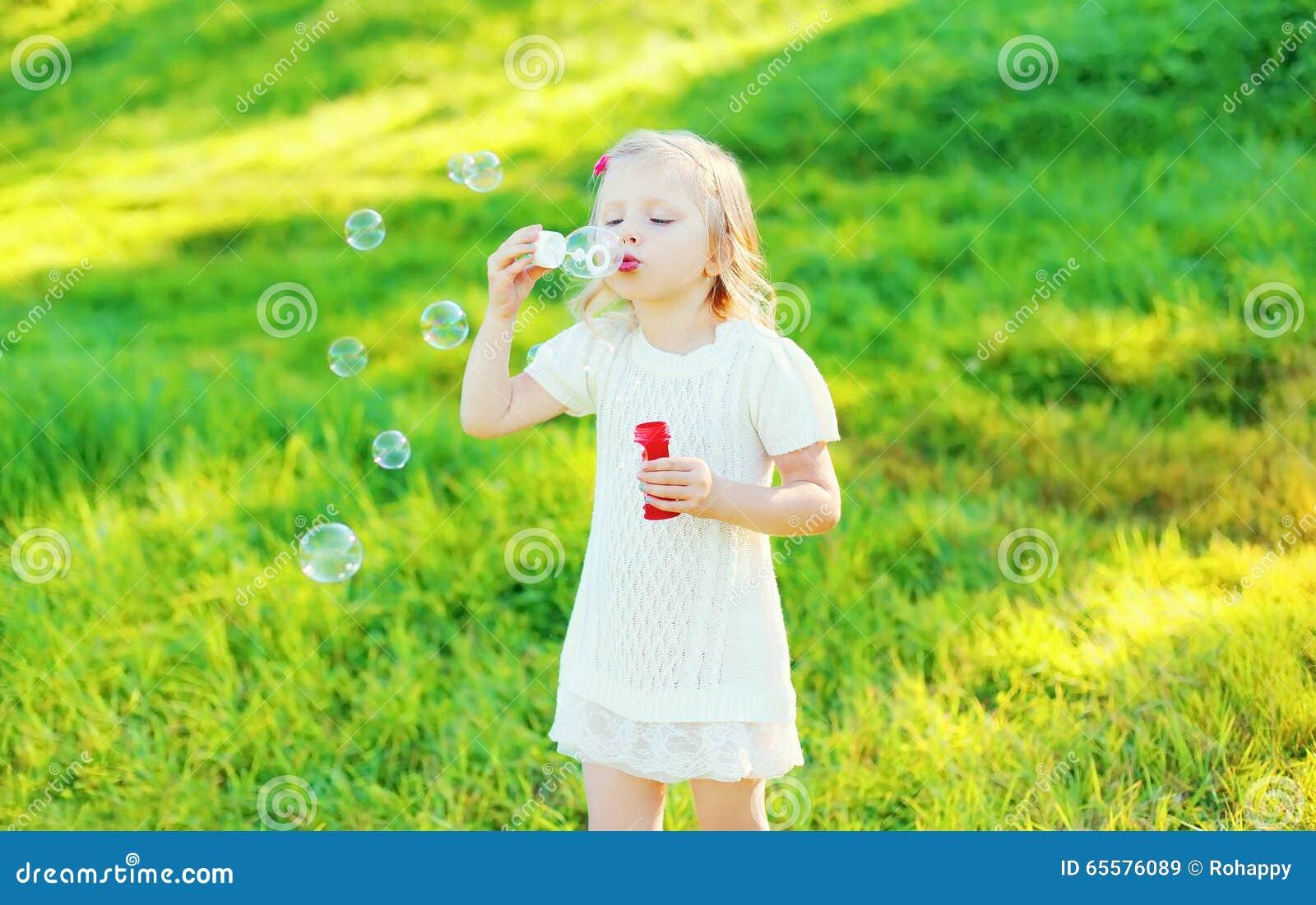 Bolhas de sabão de sopro da criança da menina no verão