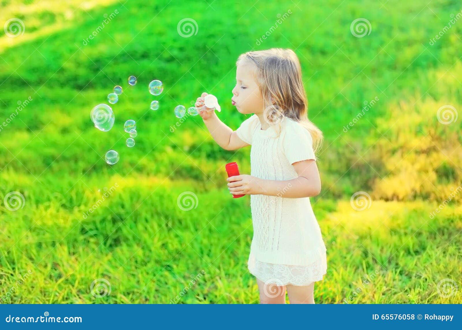 Bolhas de sabão de sopro da criança feliz da menina no verão
