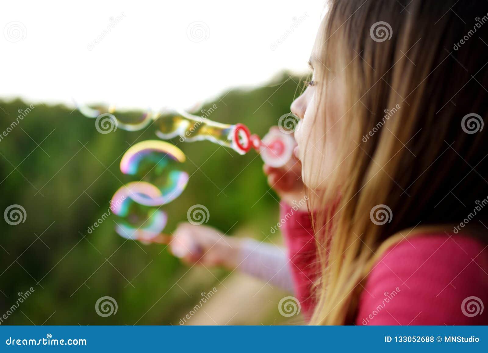 Bolhas de sabão de sopro da menina bonito em um ar livre do por do sol no dia de verão bonito