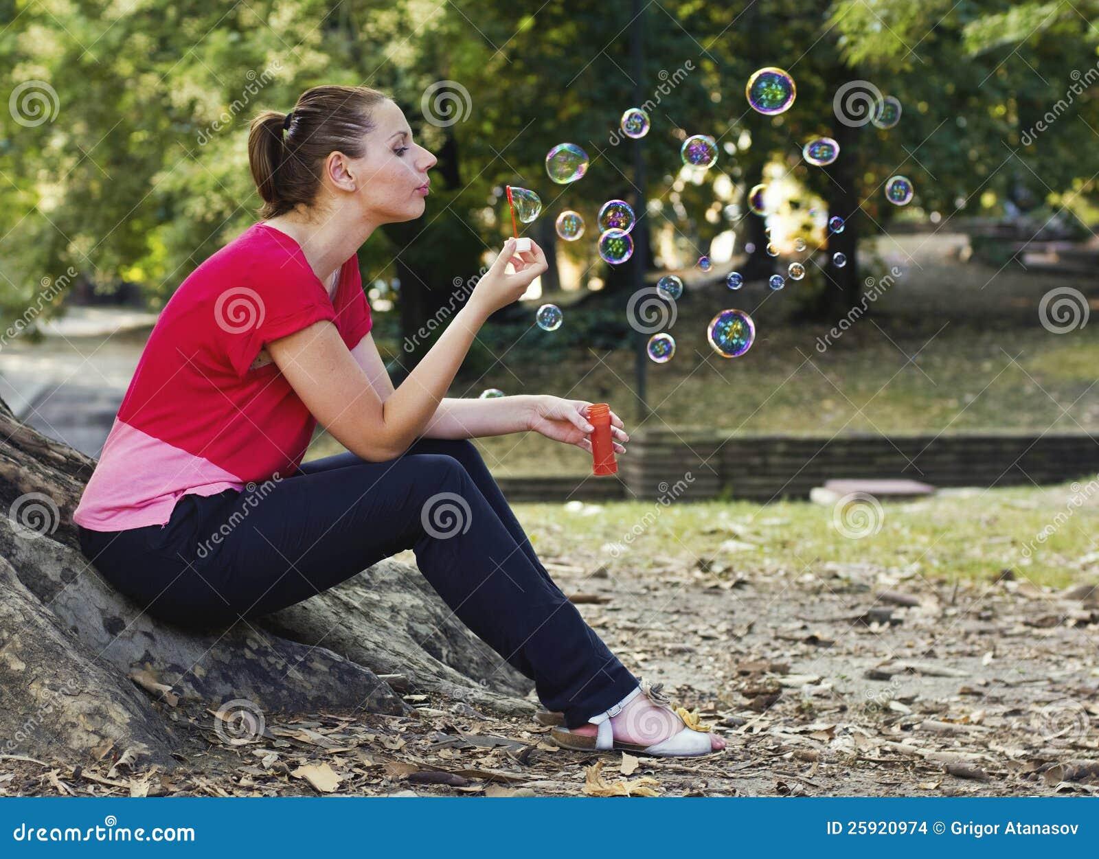 Bolhas de sopro da mulher no parque