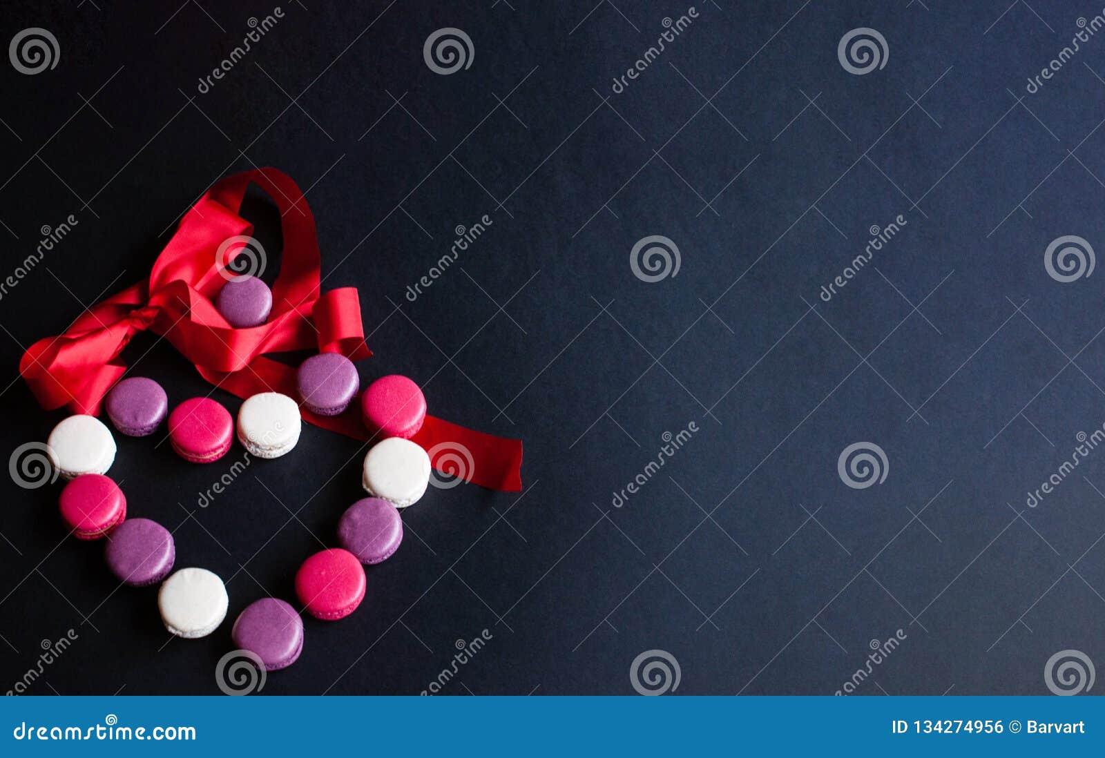 Bolinho de amêndoa apresentado em um fundo preto sob a forma de um coração com fita vermelha Cookies de amêndoa coloridas, cores