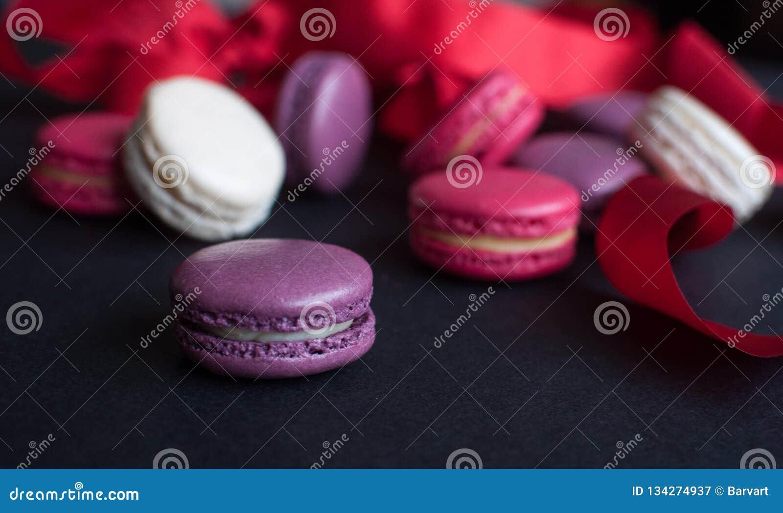 Bolinho de amêndoa no fundo preto com fita vermelha, cookies de amêndoa coloridas, cores pastel