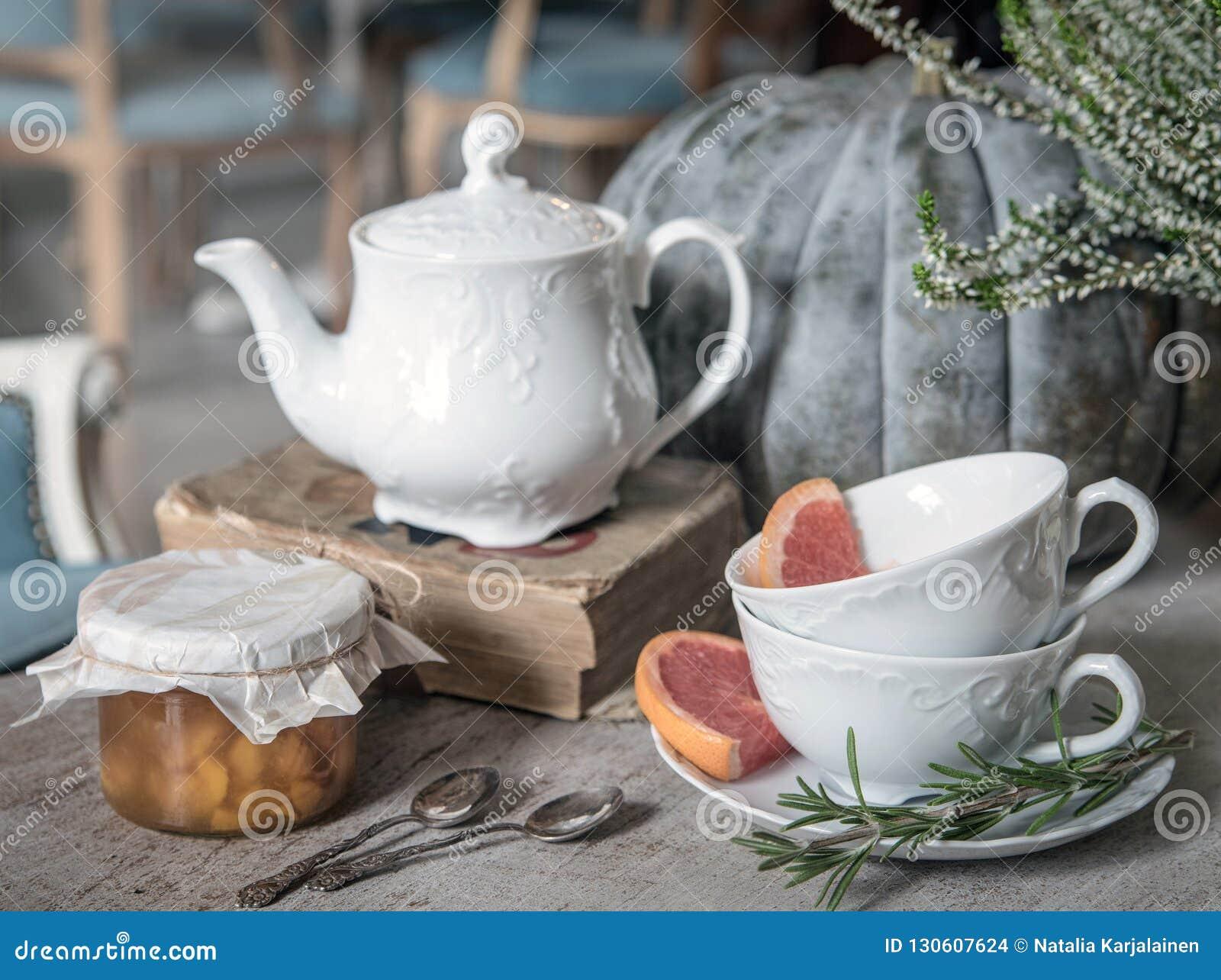 Bollitore, inceppamento, vecchio libro e tazze di tè del wo con i rosmarini ed il pompelmo sui precedenti di grandi zucca ed eric