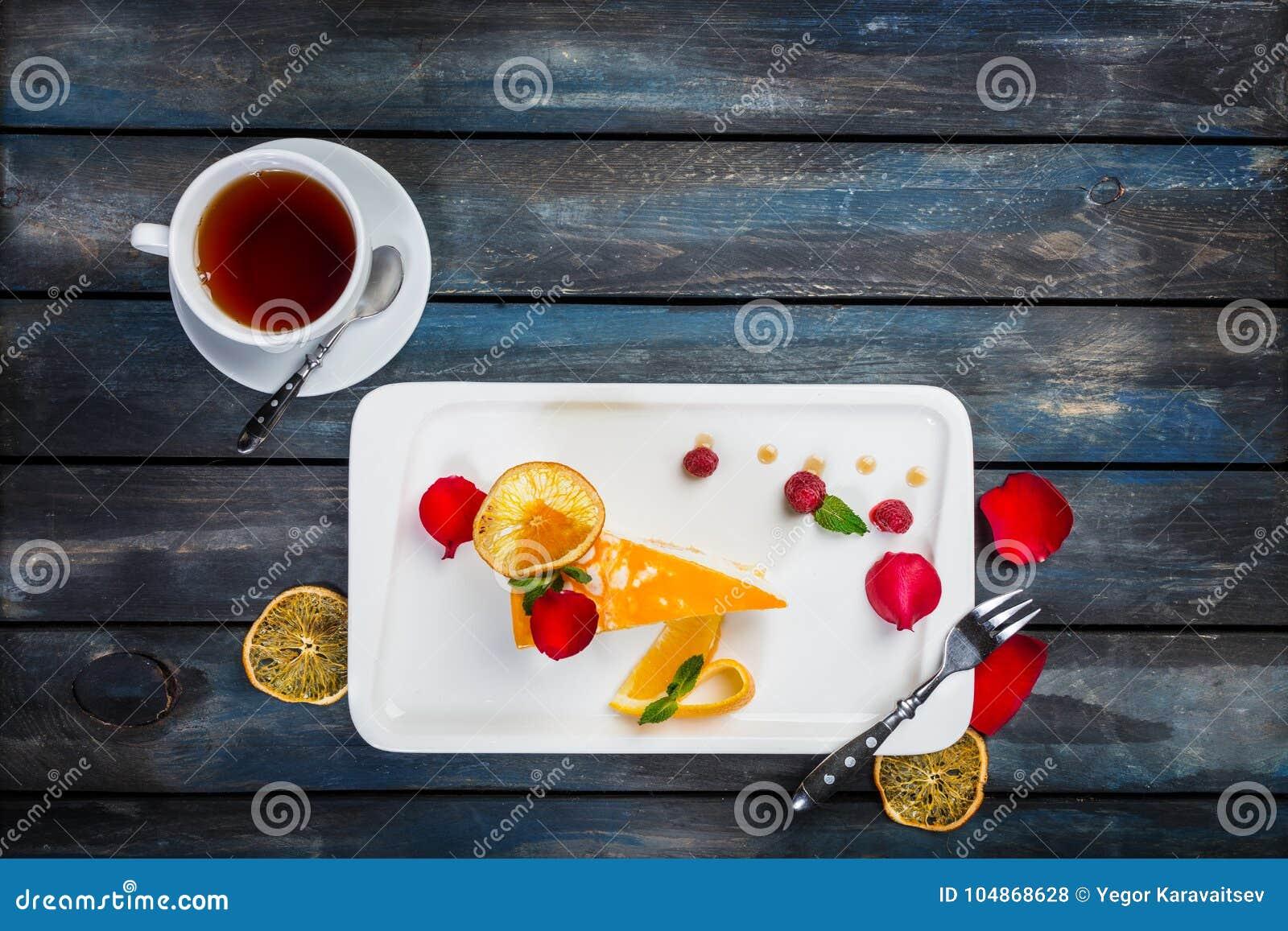 Bolo alaranjado com um copo de framboesas frescas do chá em uma placa branca com pétalas cor-de-rosa Vista superior Fundo de made