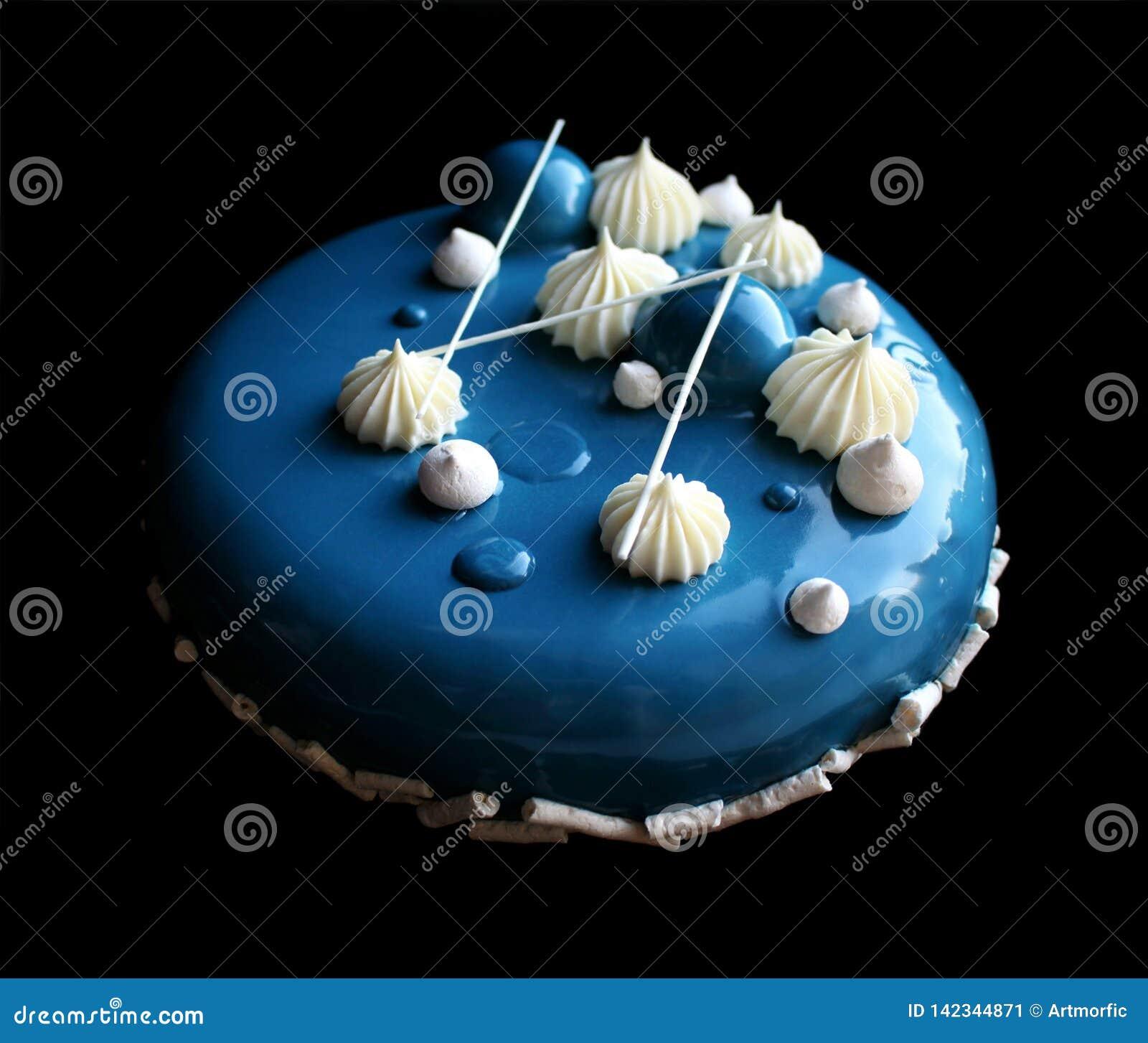 Bolo azul e branco com o bolo brilhante branco da musse com esmalte, merengues e ganache do espelho