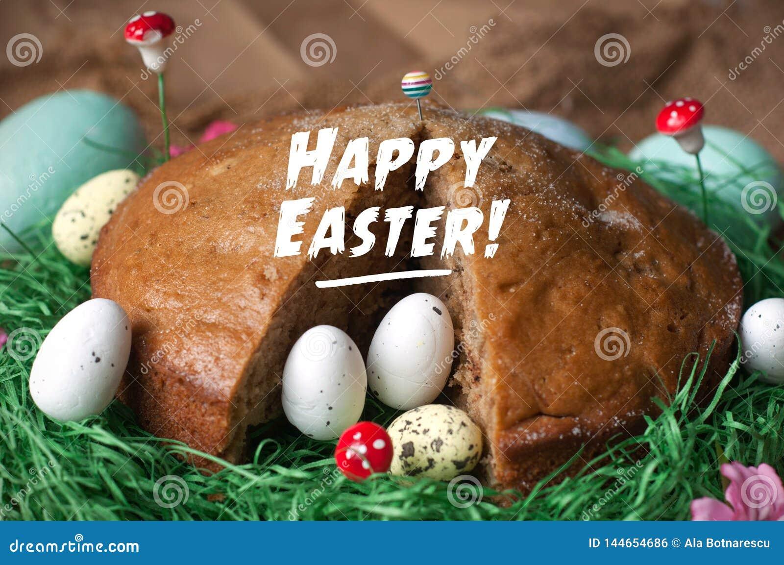 Bolo caseiro em um ninho da grama verde falsificada e dos ovos da páscoa isolados na textura do pano de saco Ramalhete feliz de C