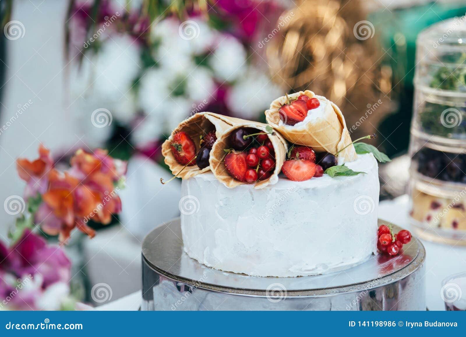 Bolo cremoso branco delicioso com os cones do waffle enchidos com as bagas diferentes nele, cercado com decorações da flor