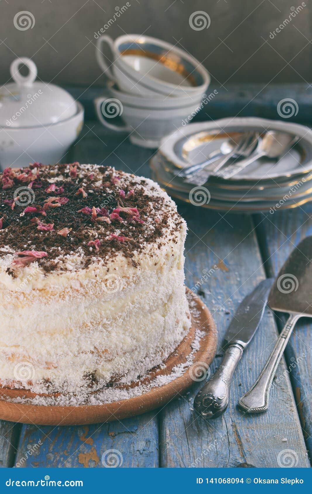 Bolo de camada delicioso do coco - biscoito e creme no creme do coco, decorado com chocolate raspado e as pétalas cor-de-rosa cri