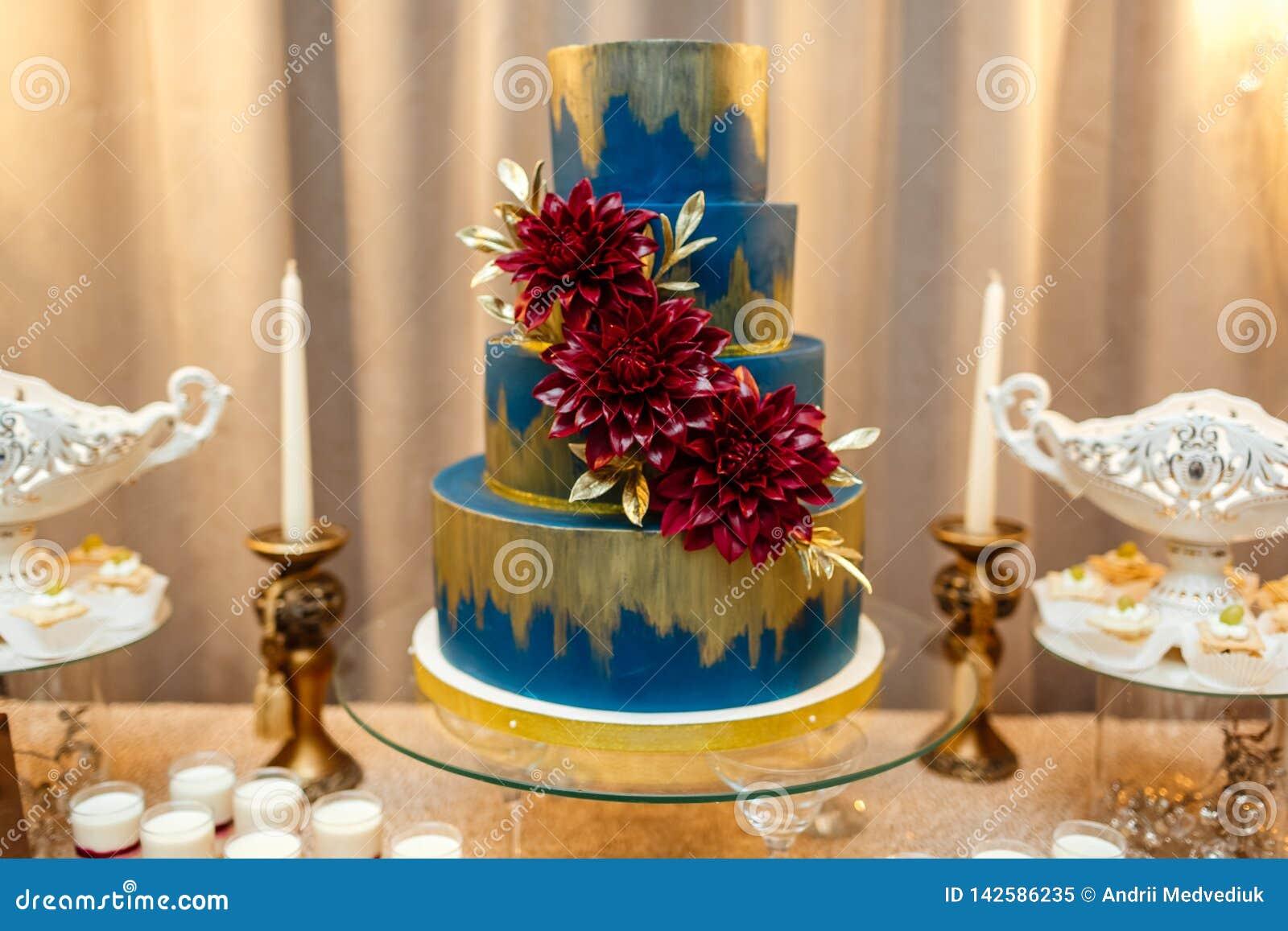 Bolo de casamento azul decorado estar das flores da tabela festiva com desertos, tartlet da morango e queques casamento