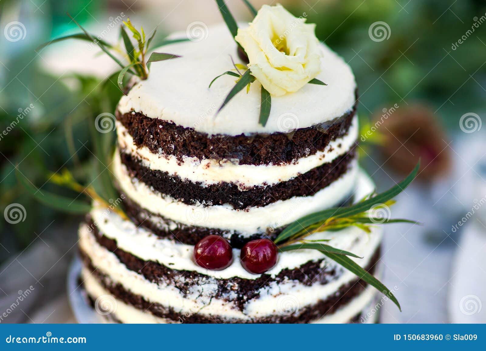Bolo de casamento bonito decorado com flores e hortaliças e cereja dois amarelas Bolo para o aniversário ou os outros feriados