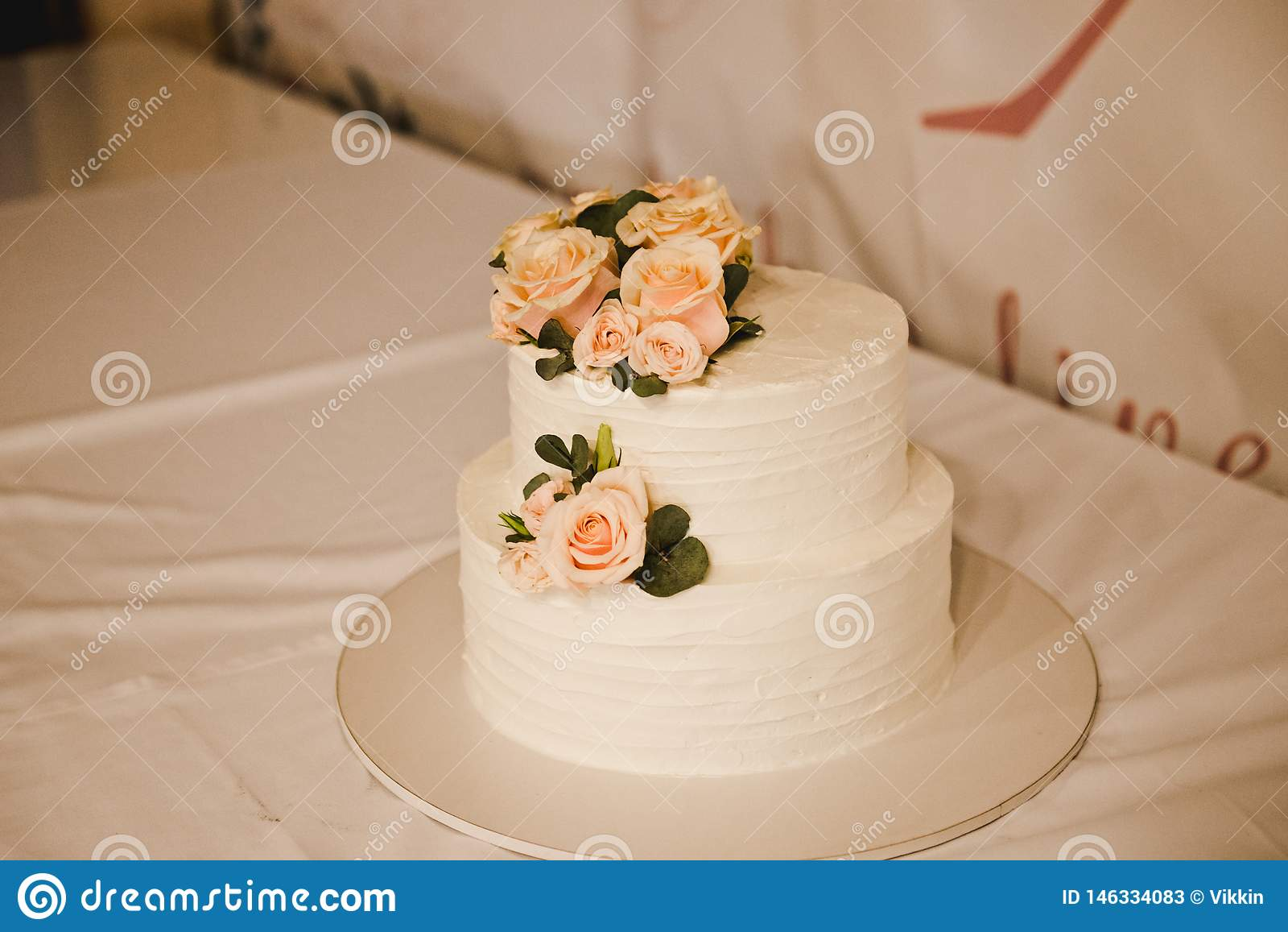 Bolo de casamento festivo com flores, flores cor-de-rosa-alaranjadas, beliche, bonito