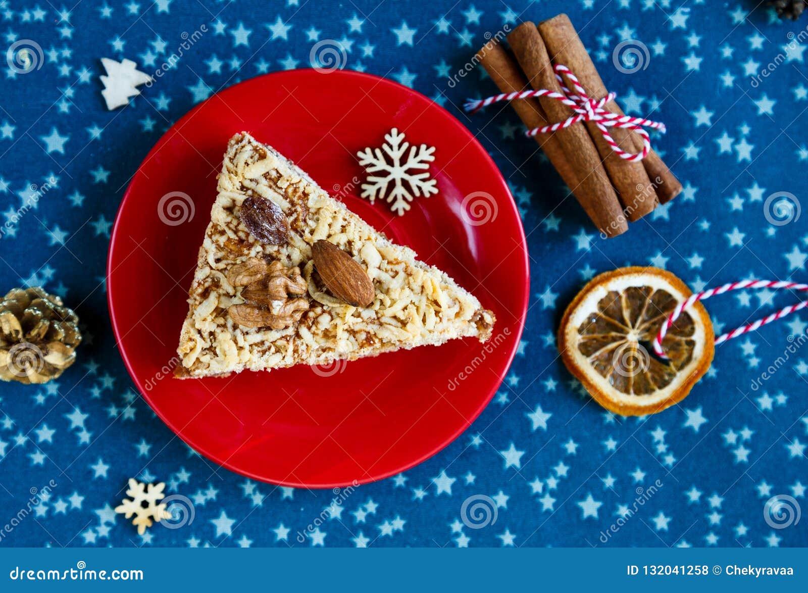 Bolo de frutas, decoração, placa com um bolo e uma xícara de café vermelha ou chá no placemat azul Ano novo