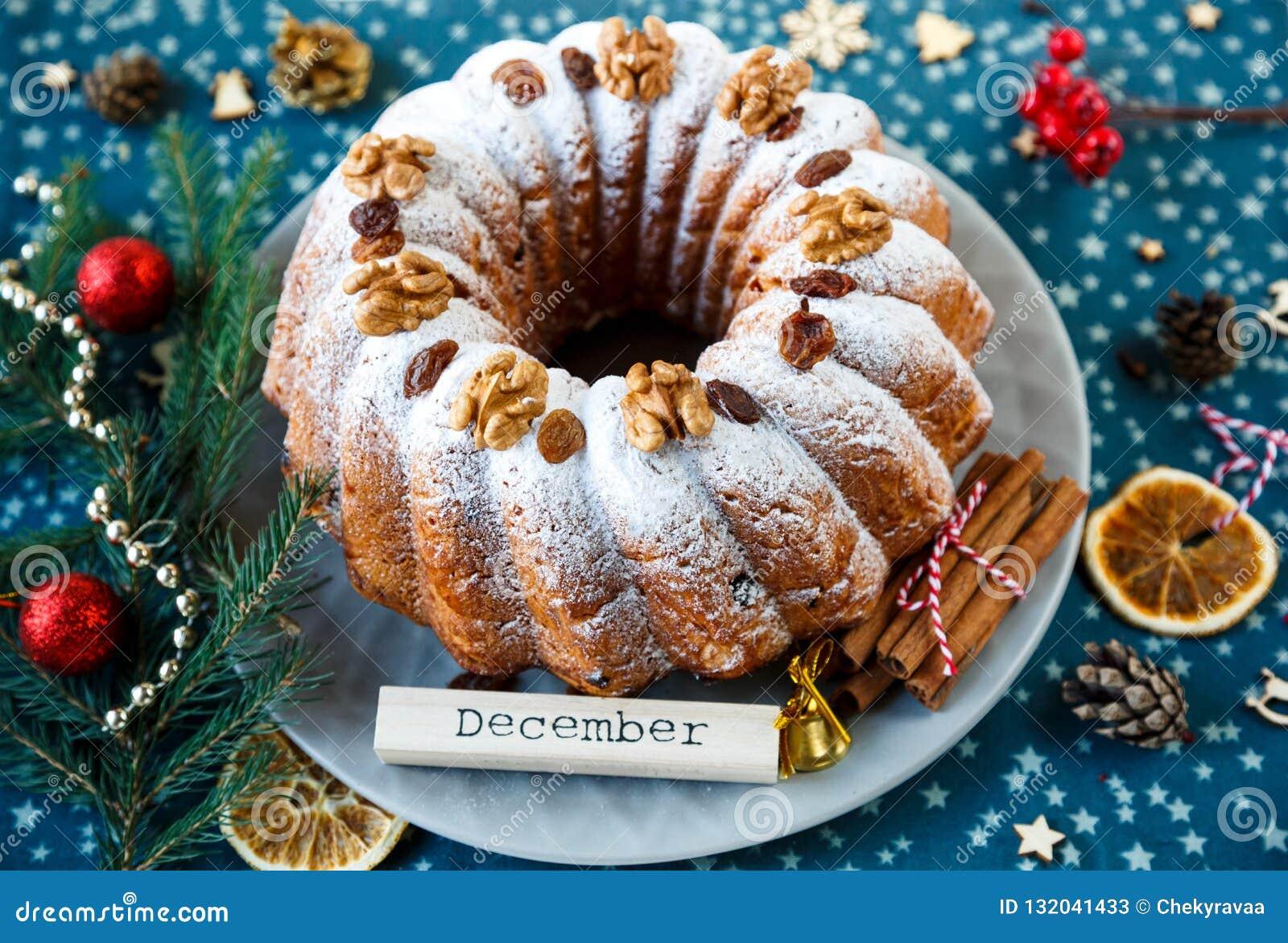 Bolo de frutas tradicional para o Natal decorado com açúcar pulverizado e porcas, passas