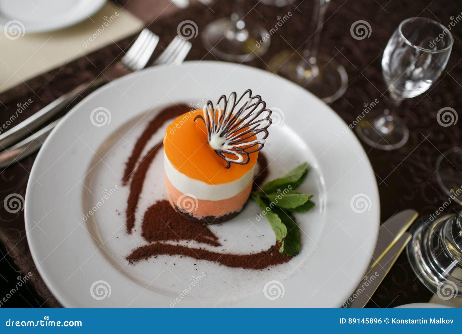 Bolo do fruto de paixão, sobremesa da musse em uma placa branca com o copo do chá Vista superior